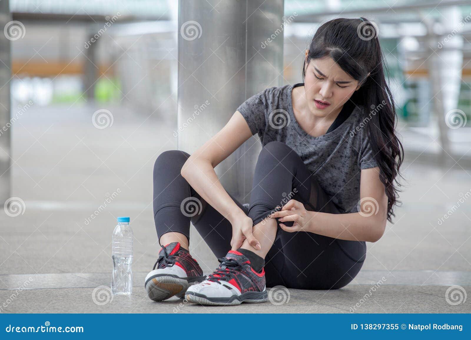 Giovane donna asiatica di forma fisica che esegue incidente della gamba di lesione dell allenamento che si esercita sulla via in