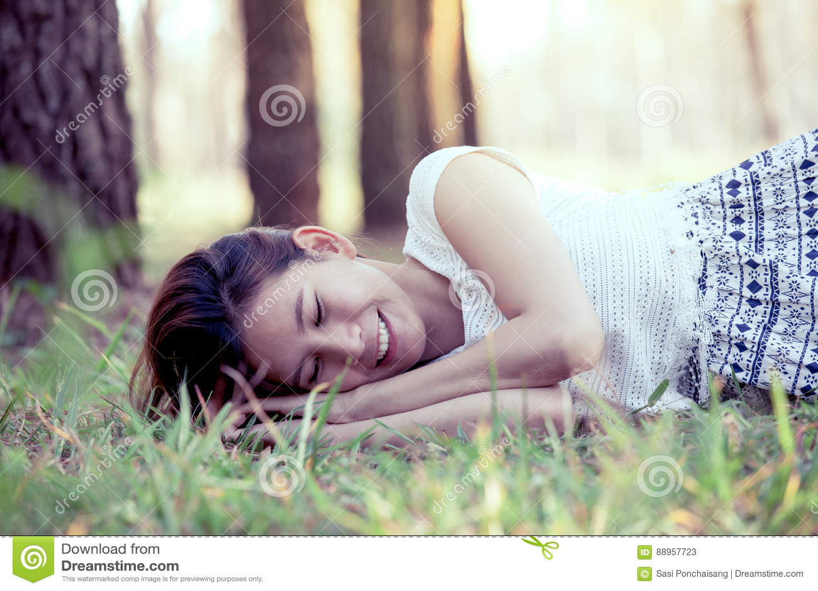 Giovane donna asiatica felice che si riposa sull erba