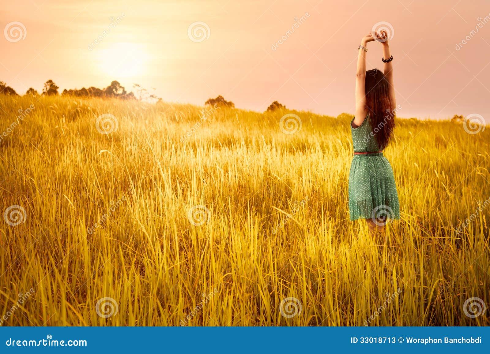 Giovane donna asiatica felice che sta nei prati