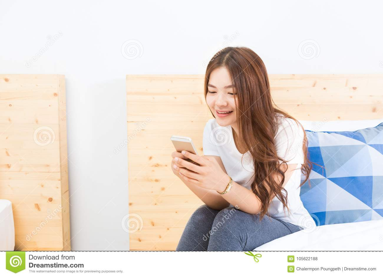 9280944076a3 Giovane donna asiatica felice che utilizza il suo Smart Phone nella sua  camera da letto