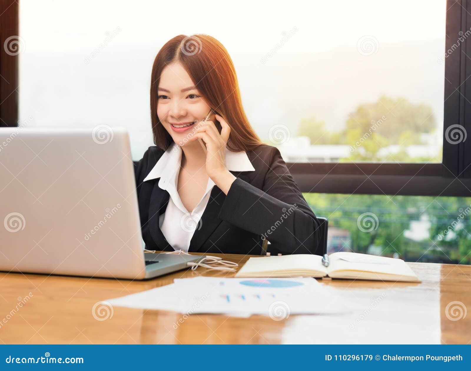 aa30cd1391cf Giovane donna asiatica felice di affari che parla sul suo telefono mentre  lavoro