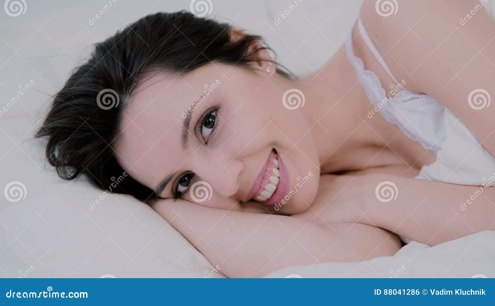 Giovane donna attraente che sveglia a letto a casa La ragazza guarda alla macchina fotografica ed ai sorrisi svegli Donna fresca