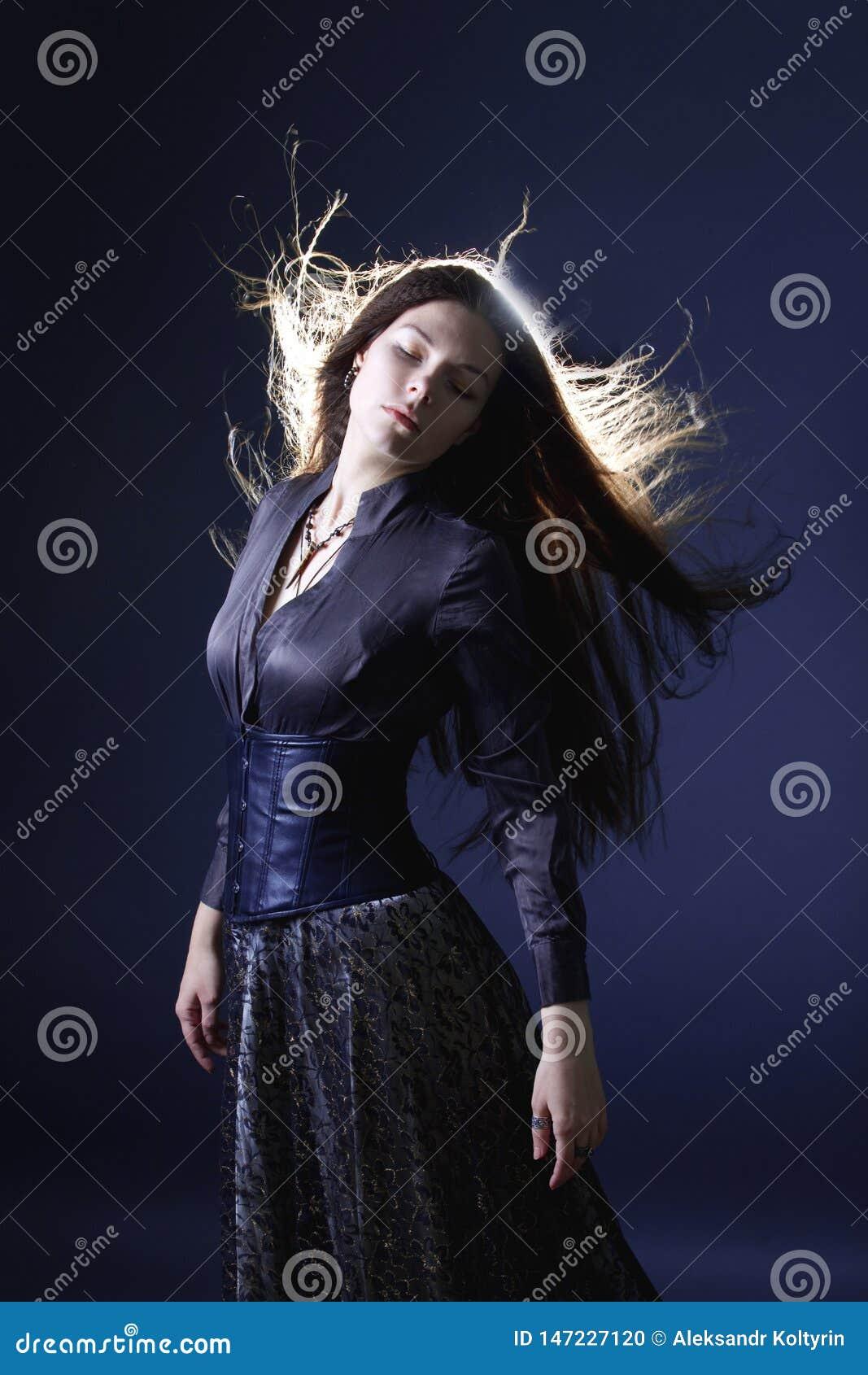 Giovane donna attraente con capelli lunghi come una strega Femme castana, stile mistico di fantasia