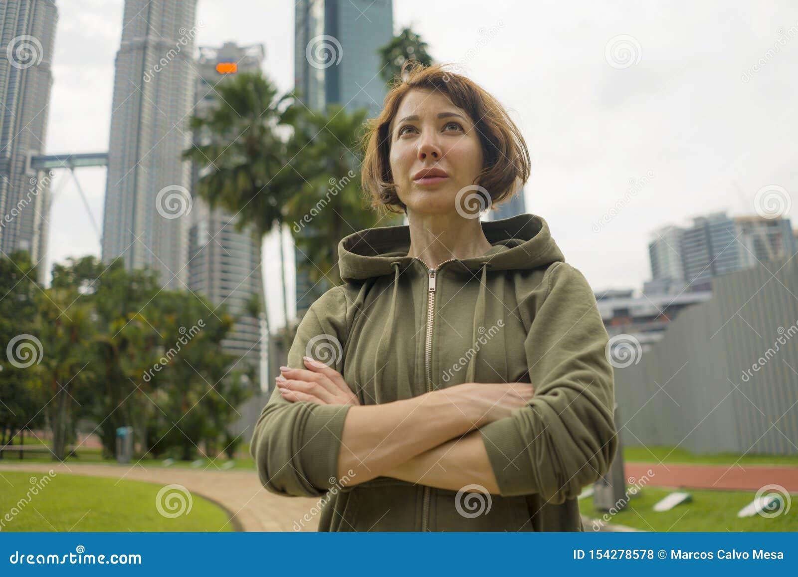 Giovane donna attraente e attiva del pareggiatore nella cima di maglia con cappuccio pronta per la mattina che esegue allenamento