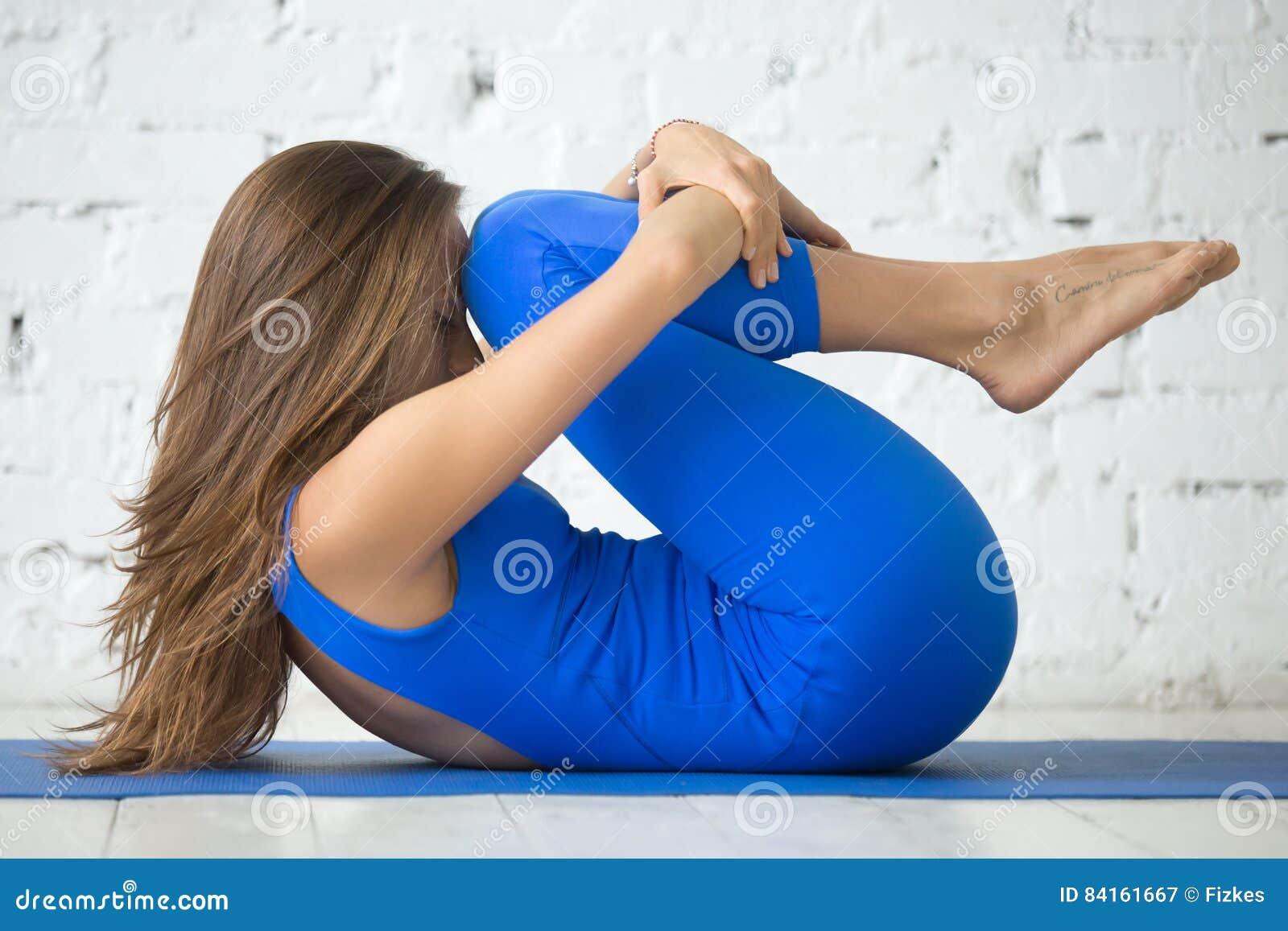 Giovane donna attraente in ginocchia alla posa del petto, studio bianco