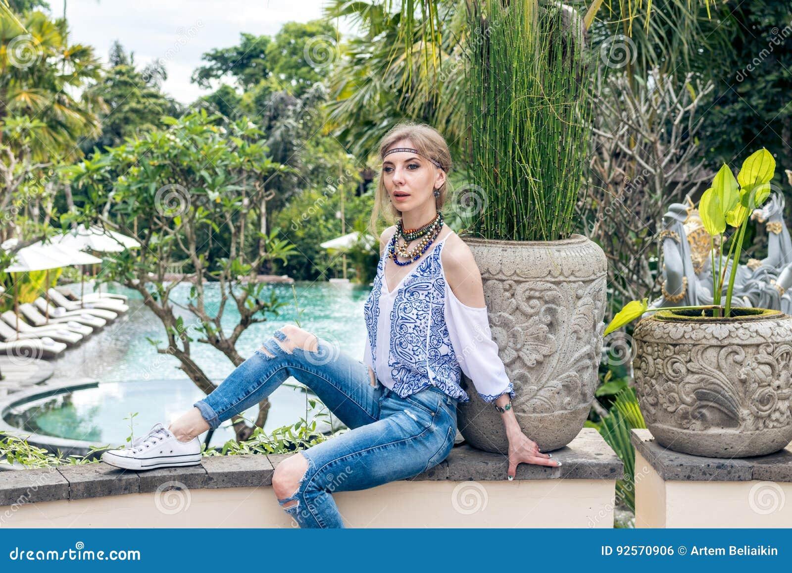 Giovane donna attraente nel sembrare etnico che posa vicino alla piscina, ritratto di stile Isola tropicale Bali, località di sog