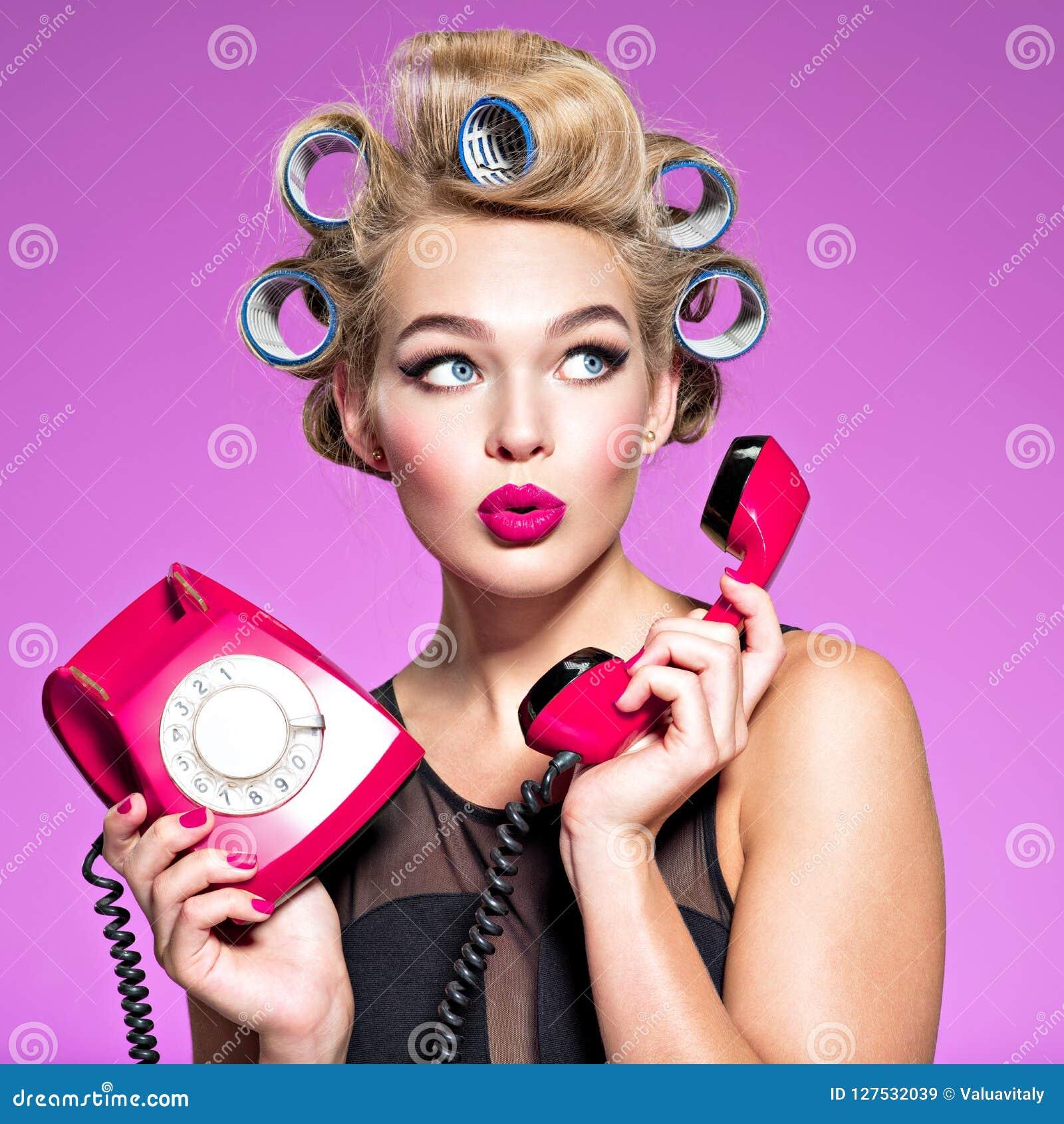 Giovane donna attraente sorpresa dopo la conversazione sul telefono