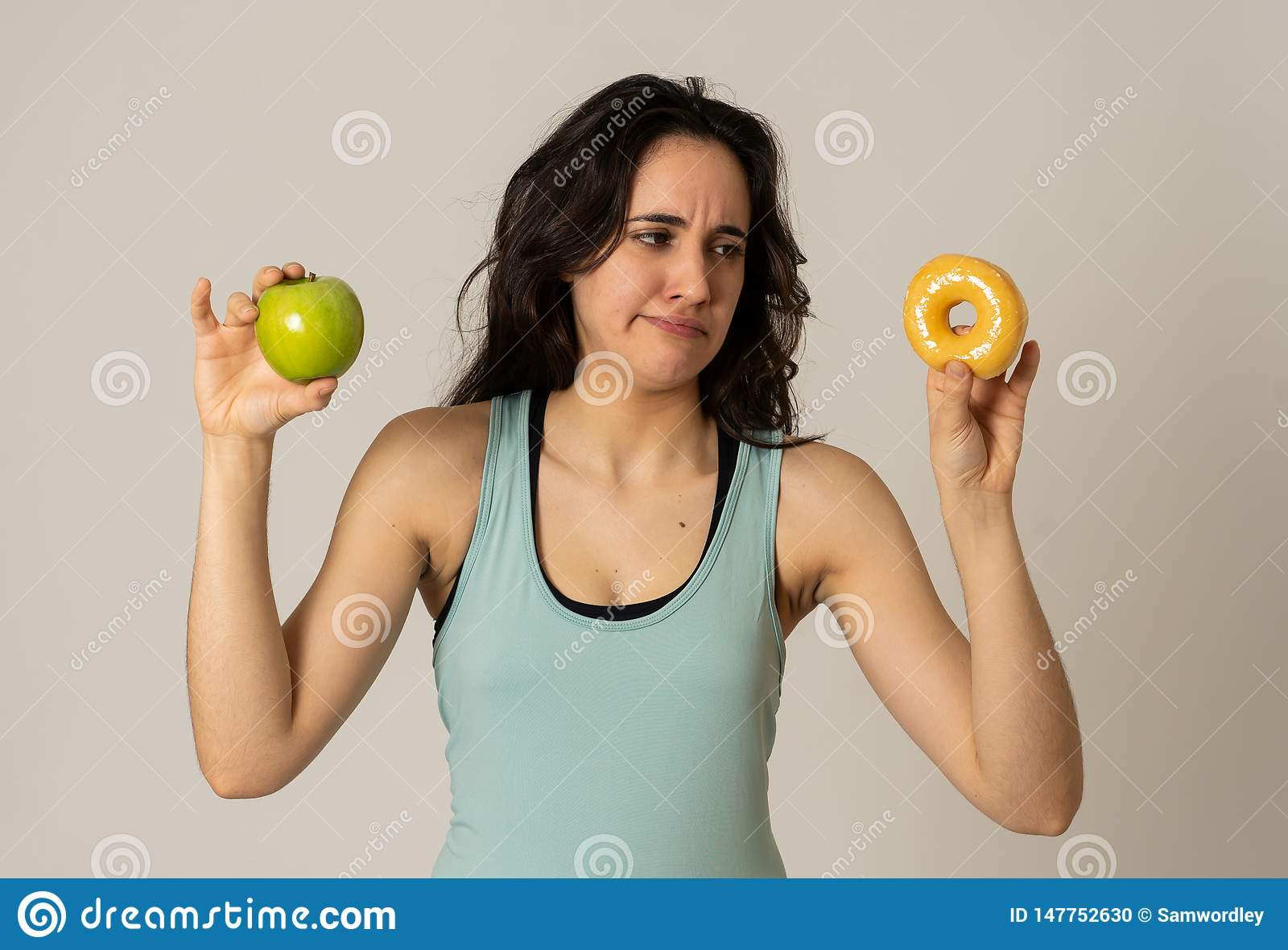 Giovane donna attraente su una dieta che decide fra una mela e una ciambella