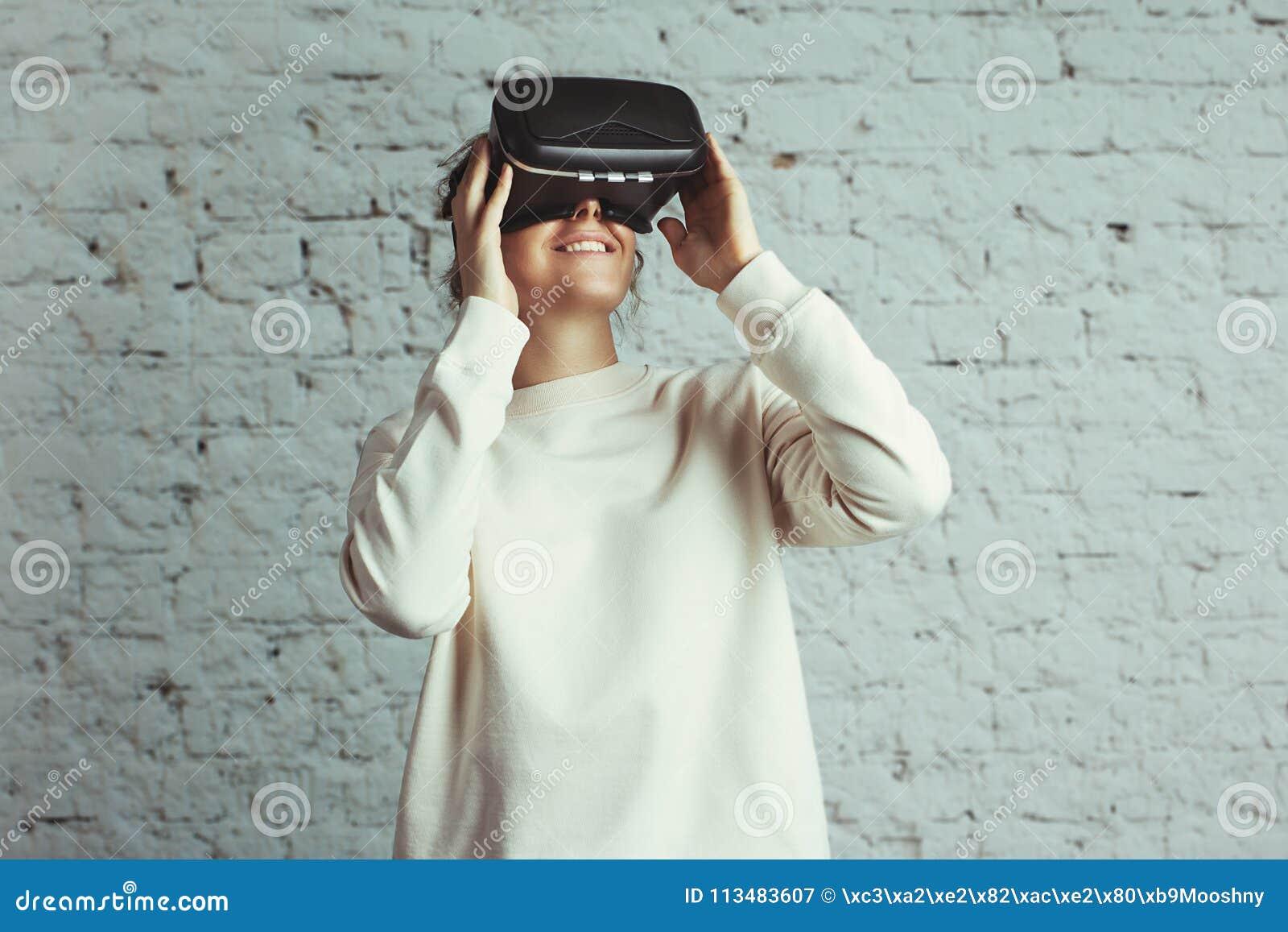 Giovane donna bella che indossa cuffia avricolare virtuale Pantaloni a vita bassa sorridenti che usando i vetri di VR Maglione in