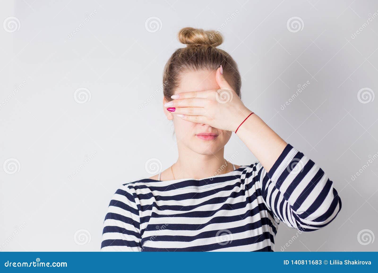 Giovane donna bionda attraente che chiude i suoi occhi con le mani Ritratto di bella ragazza, concetto di sorpresa