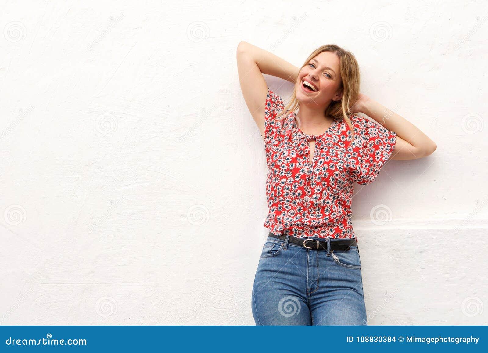 Giovane donna bionda che ride con le mani dietro la testa