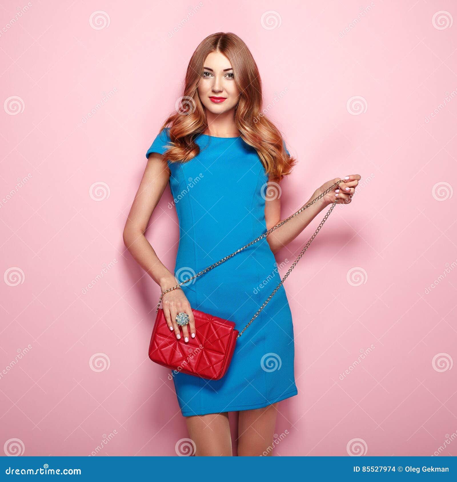 2231c45ac9fb Giovane donna bionda in vestito blu elegante Ragazza che posa su un fondo  rosa Gioielli e acconciatura Ragazza con la borsa rossa Foto di modo