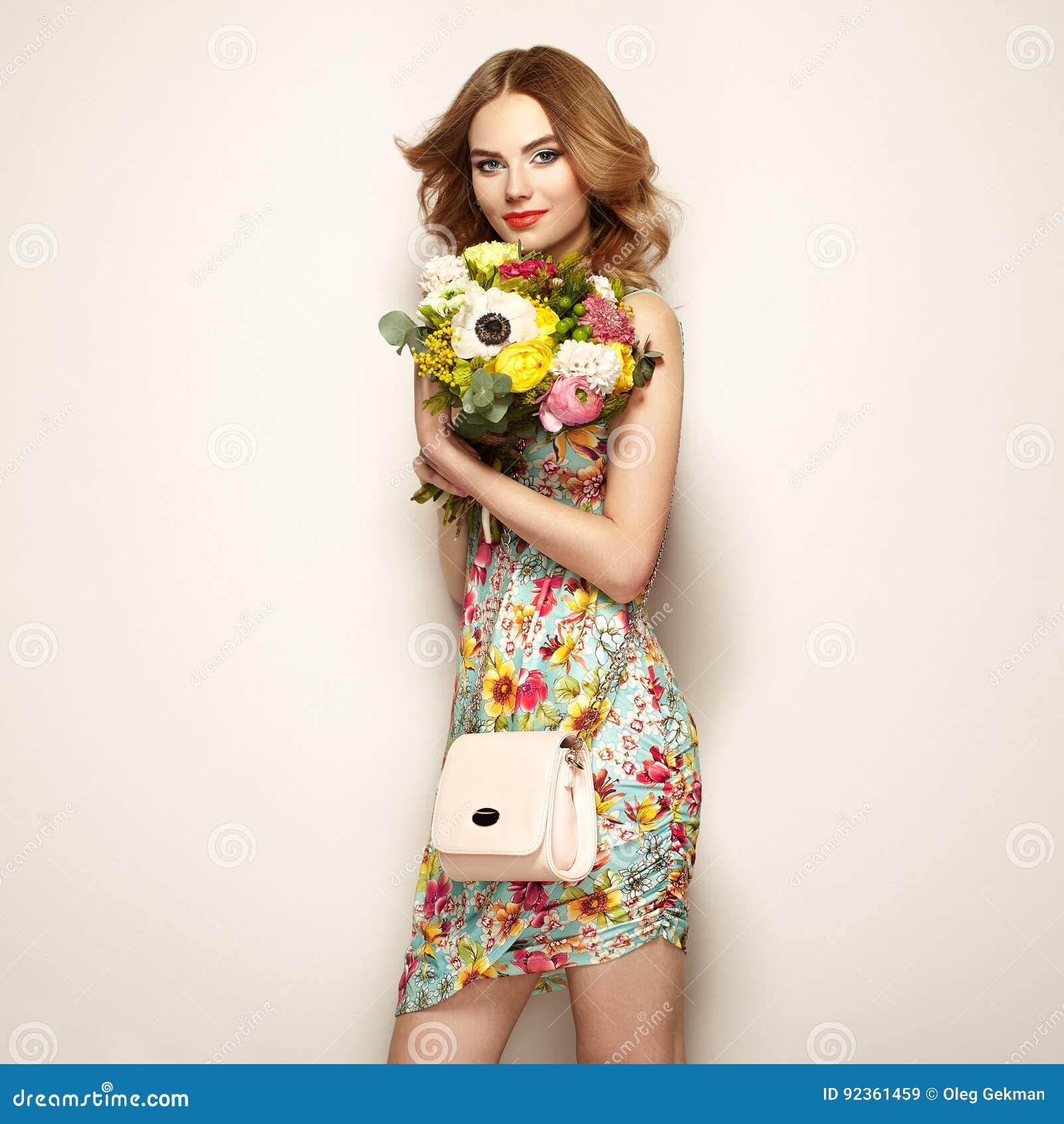 ab4849010db9 Giovane donna bionda in vestito floreale elegante Ragazza che posa su un  fondo beige con la borsa Gioielli e acconciatura Signora con il mazzo della  molla ...