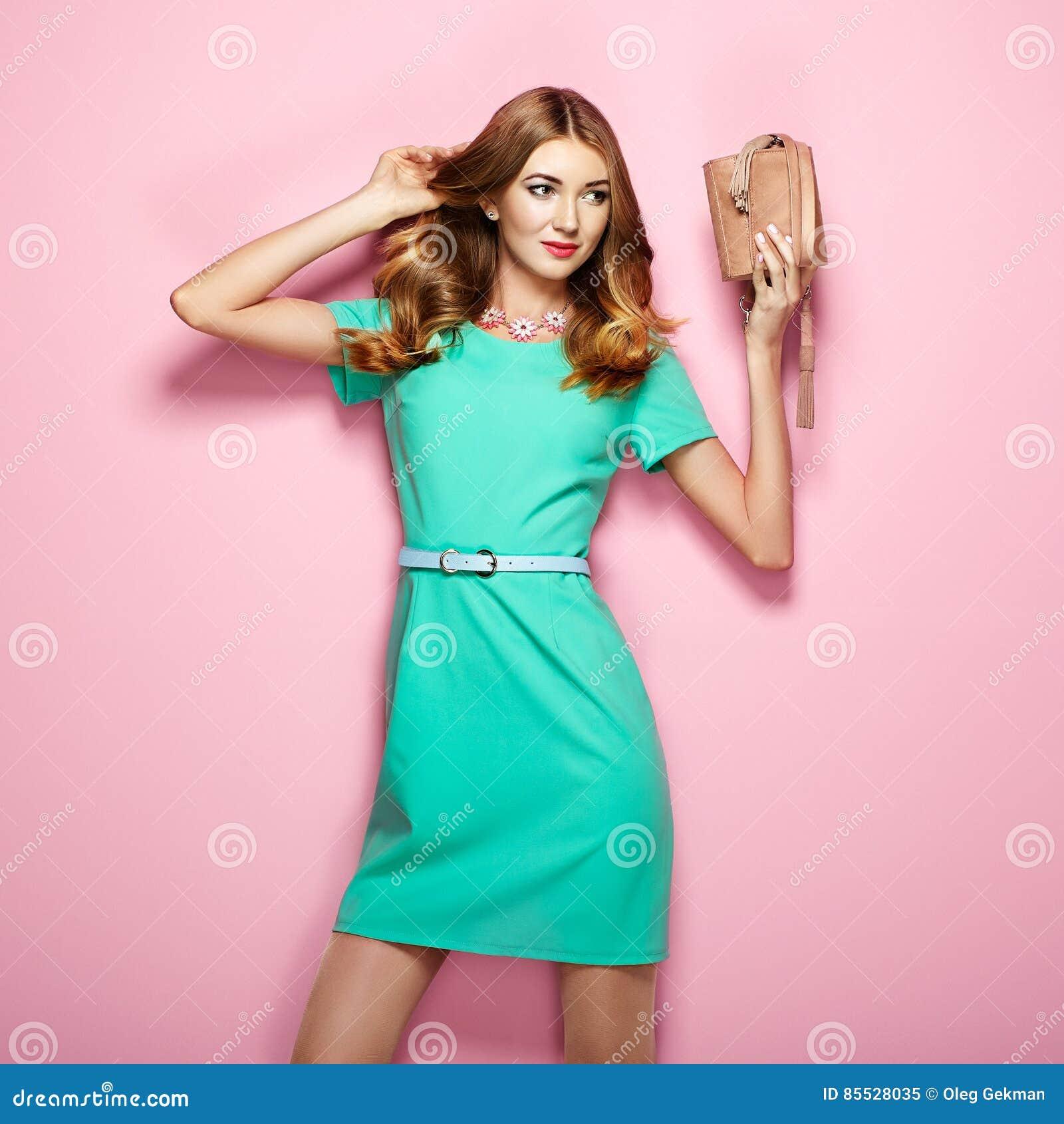864adf17dd40 Giovane donna bionda in vestito verde elegante Ragazza che posa su un fondo  rosa Gioielli e acconciatura Ragazza con la borsa Foto di modo
