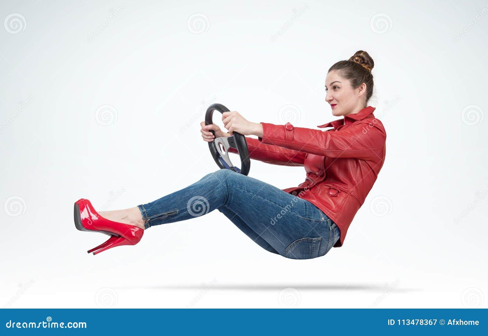 Giovane donna in bomber rosso con il volante dell automobile, concetto automatico