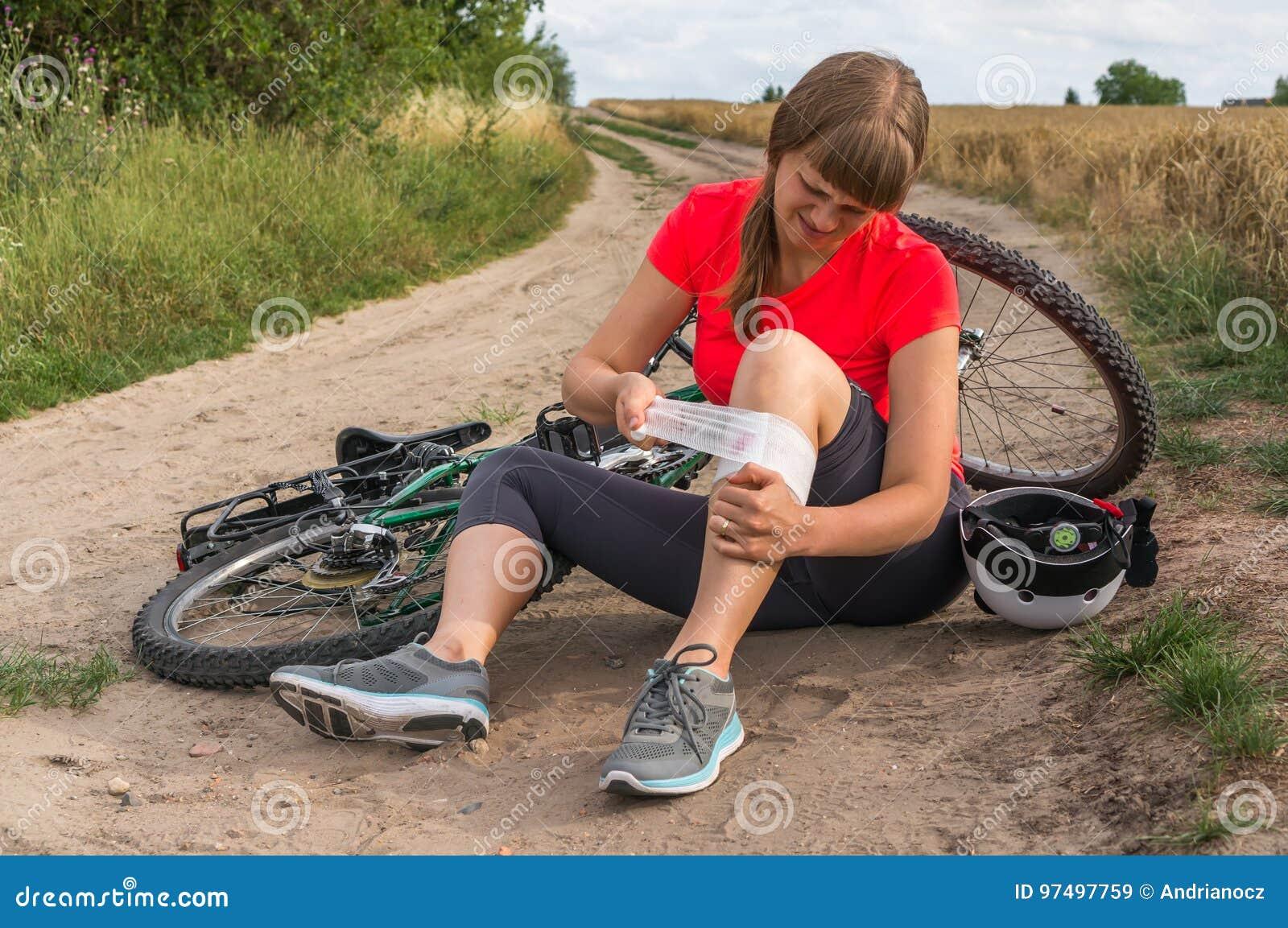 Giovane donna caduta dalla bicicletta della montagna