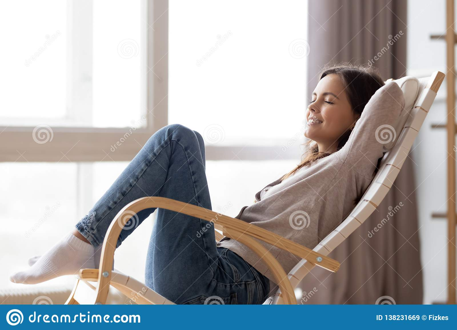 Giovane donna calma rilassata che bighellona seduta nella sedia di oscillazione comoda