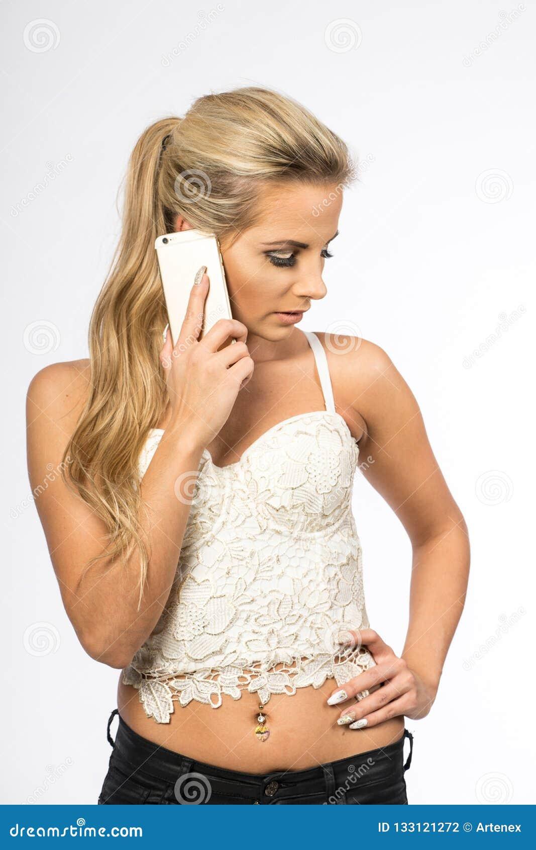 Giovane donna in camicetta bianca La ragazza bionda sta parlando sul telefono cellulare Femmina con il telefono Chiamate della do