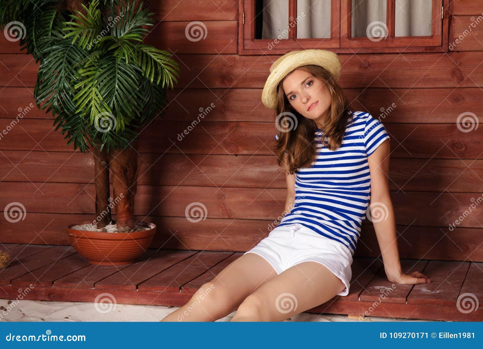 Giovane donna in cappello di paglia che si siede vicino al bungalow di legno