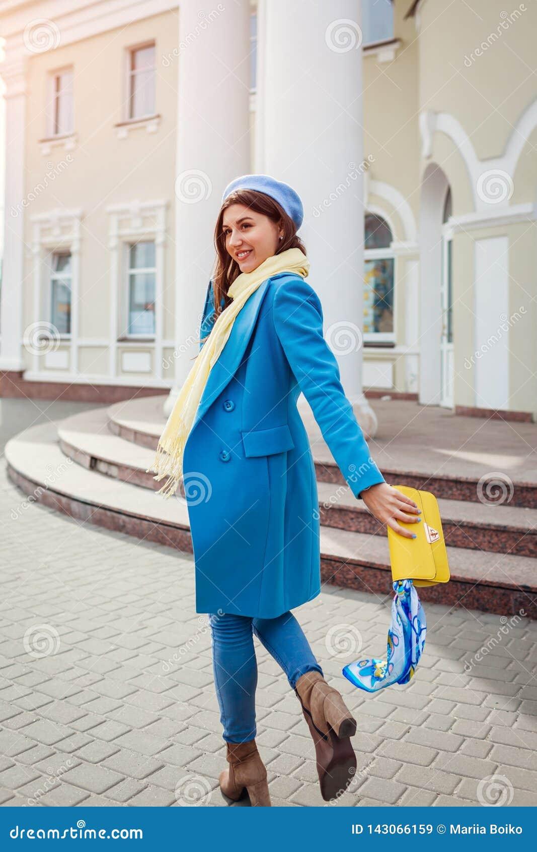 Giovane donna in cappotto blu d avanguardia che cammina nella città che tiene borsa alla moda Vestiti ed accessori femminili dell