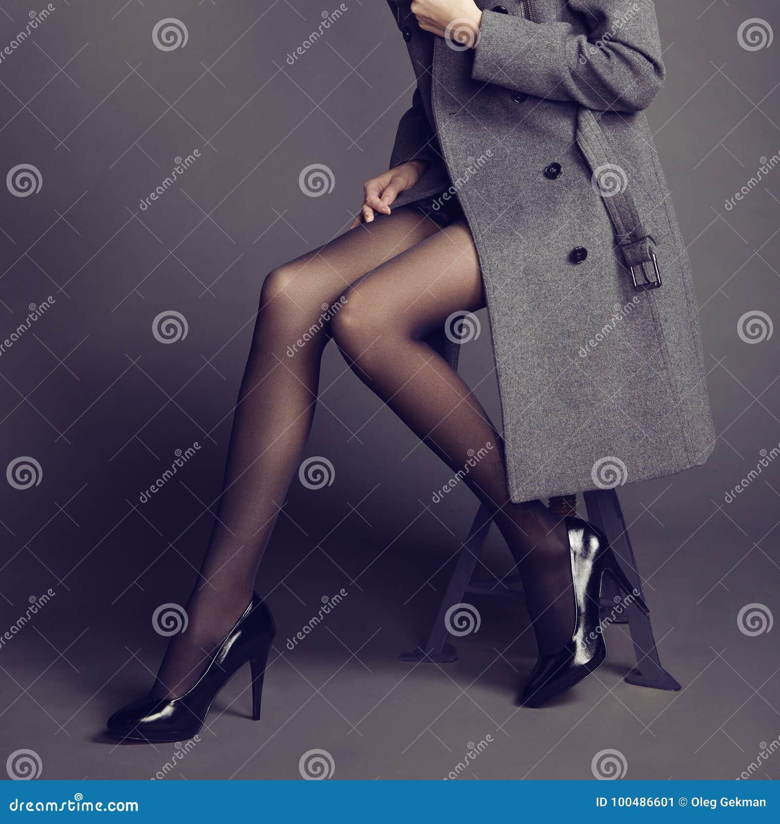 Giovane donna in cappotto con i bei piedi