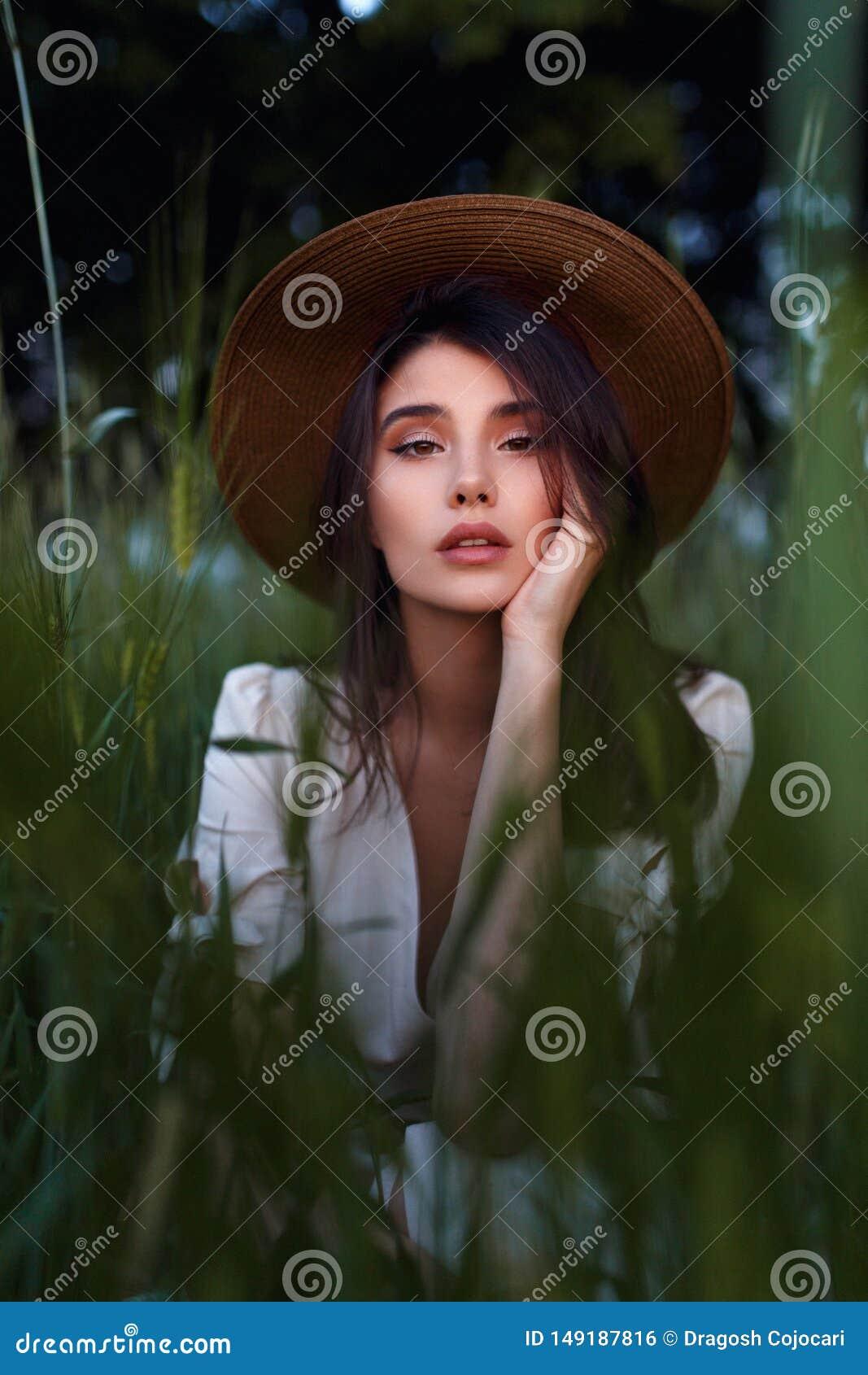 Giovane donna castana adorabile spensierata in attrezzatura romantica, con la mano sul suo fronte nel campo verde Concetto di cur