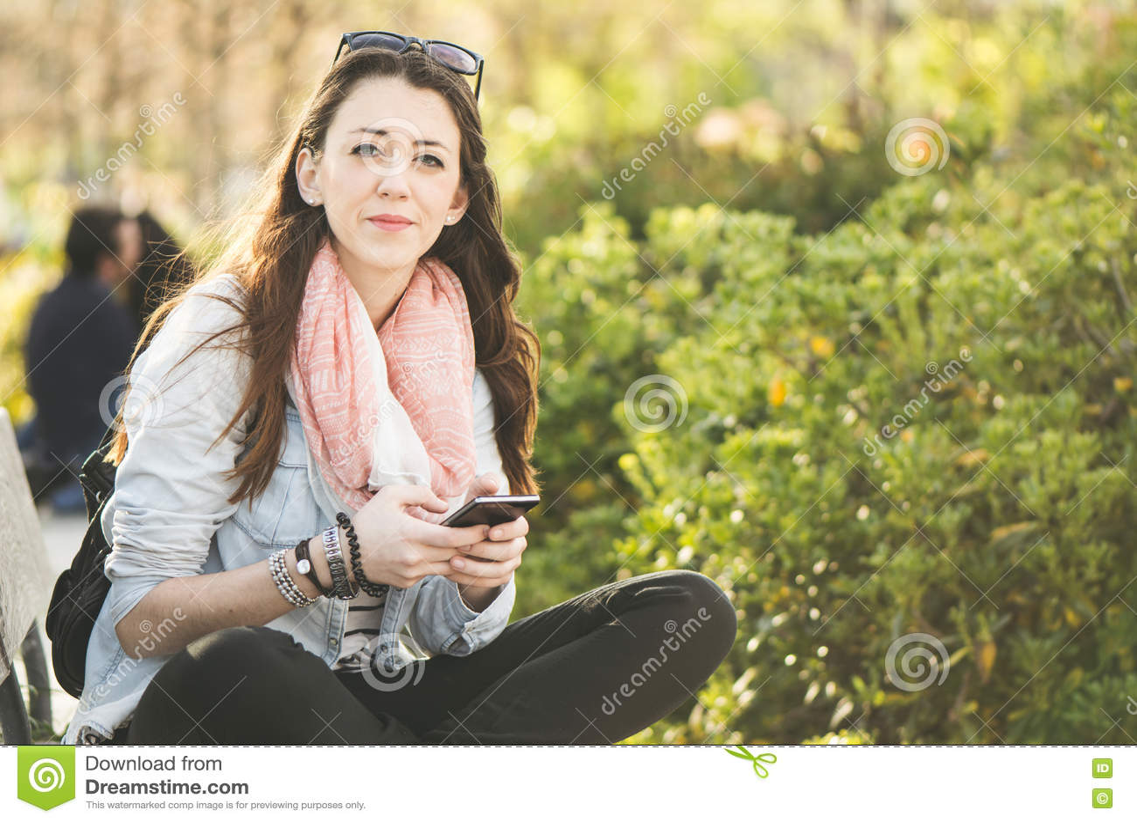 Giovane donna castana con il telefono a disposizione, sedendosi nel parco