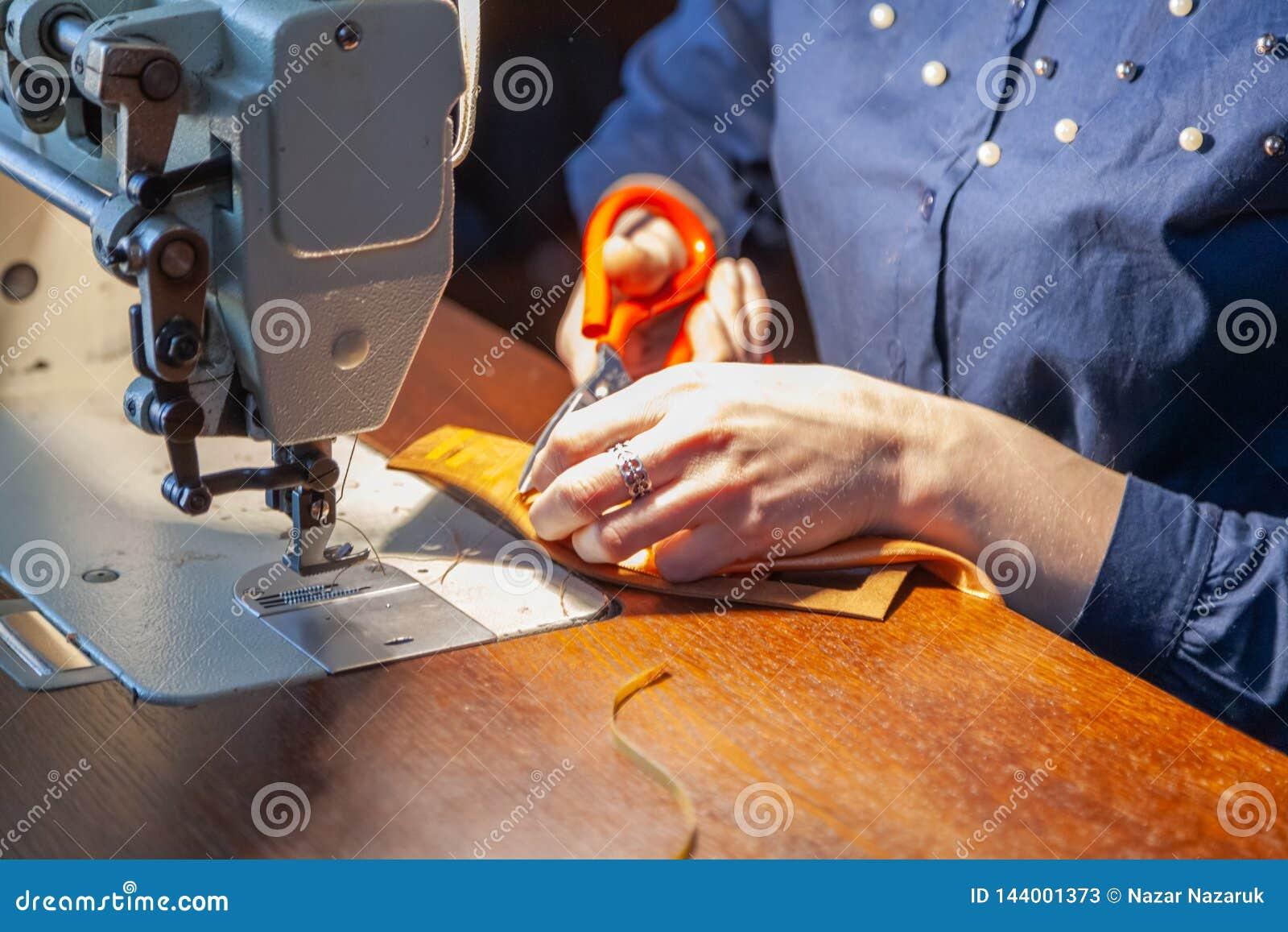 Giovane donna che adatta sulla macchina per cucire