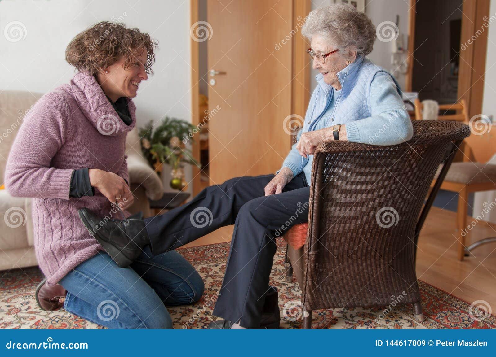 Giovane donna che aiuta signora senior che intraprende le sue scarpe