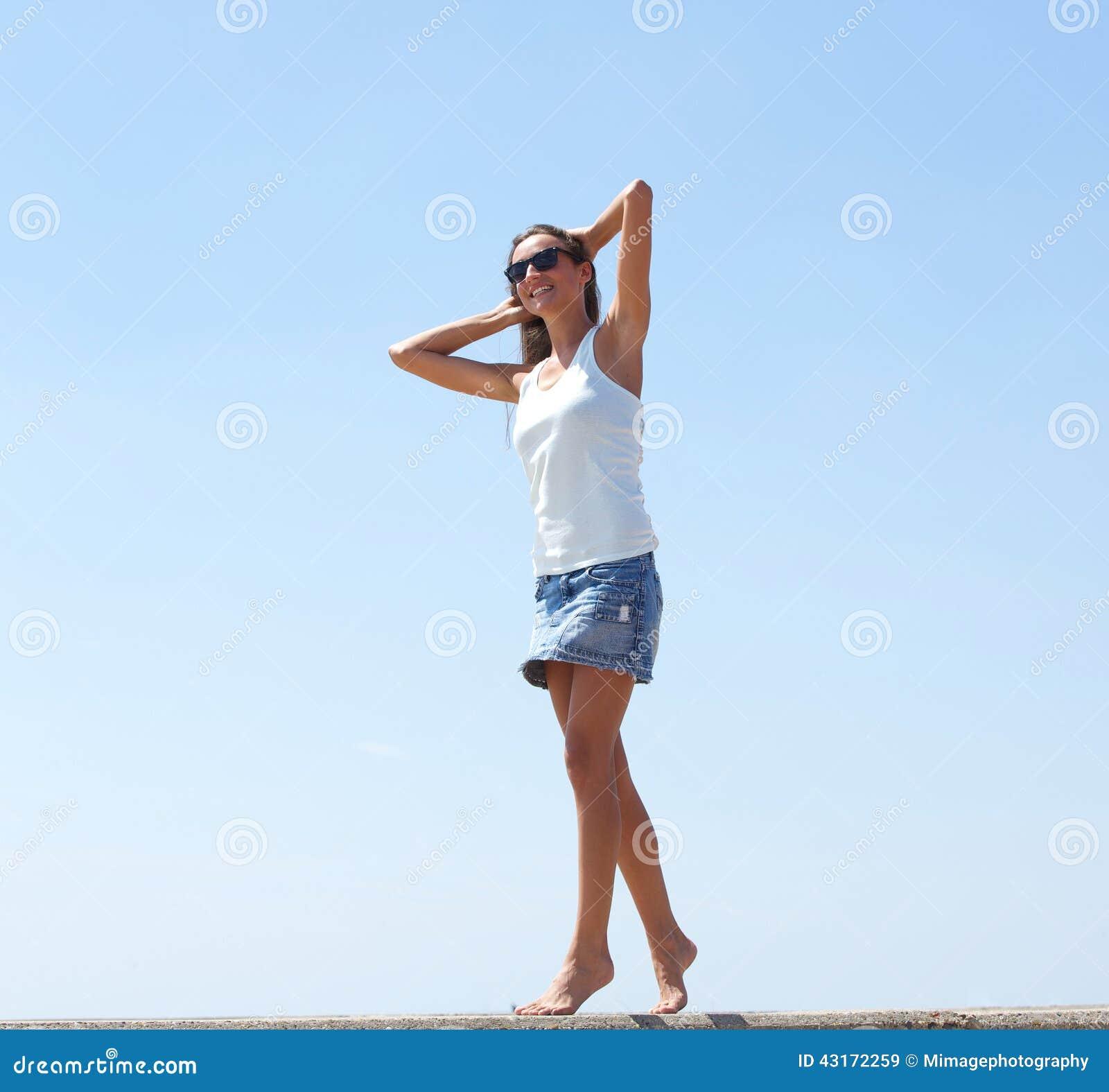 Giovane donna che cammina con la mano in capelli