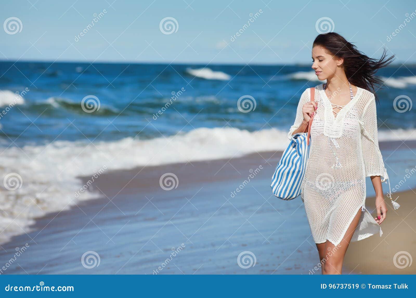 Giovane donna che cammina in vestito bianco d uso dalla spiaggia dell acqua