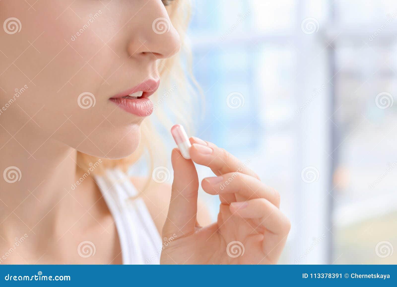 Giovane donna che cattura pillola