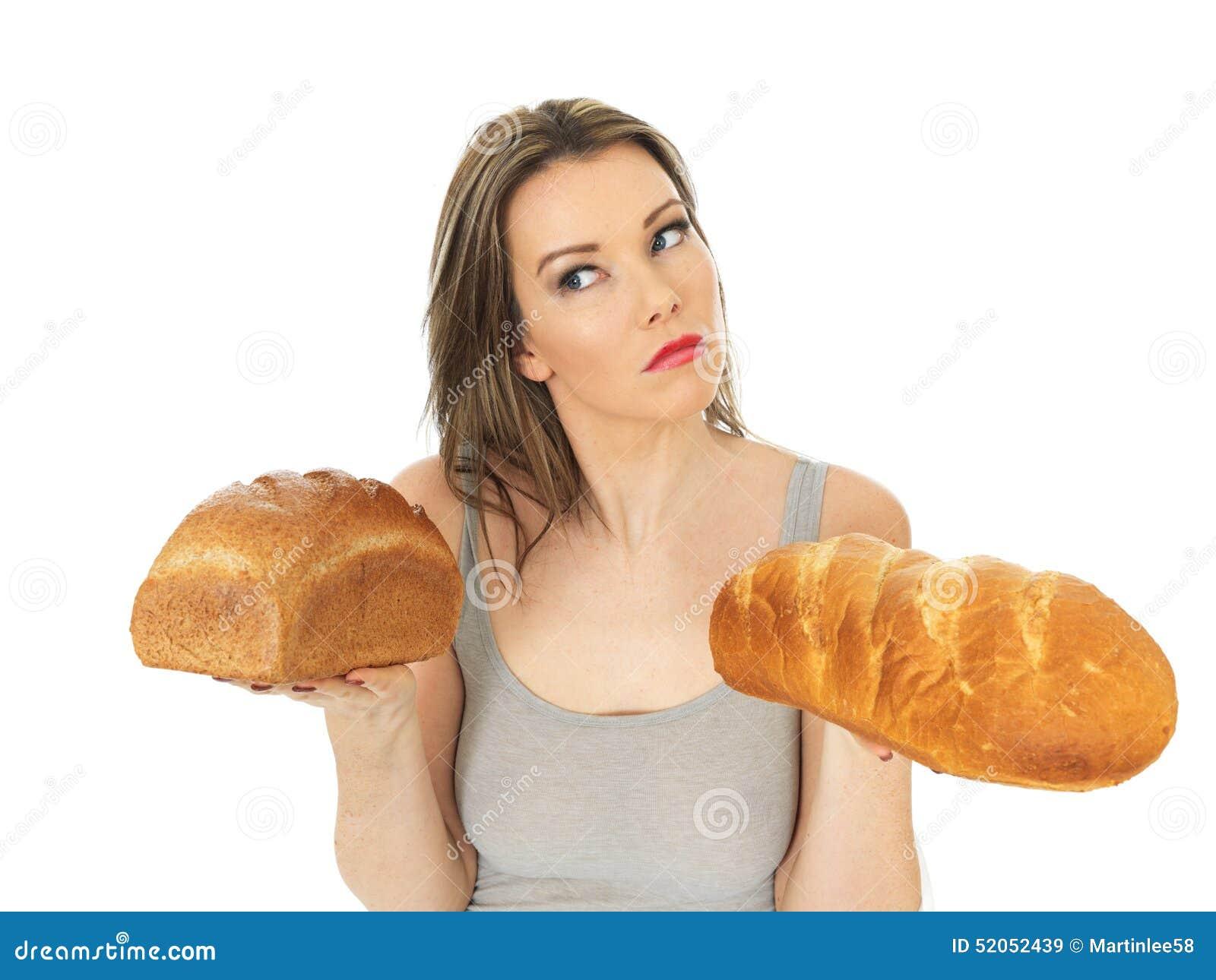 Giovane donna che confronta bianco e pane nero