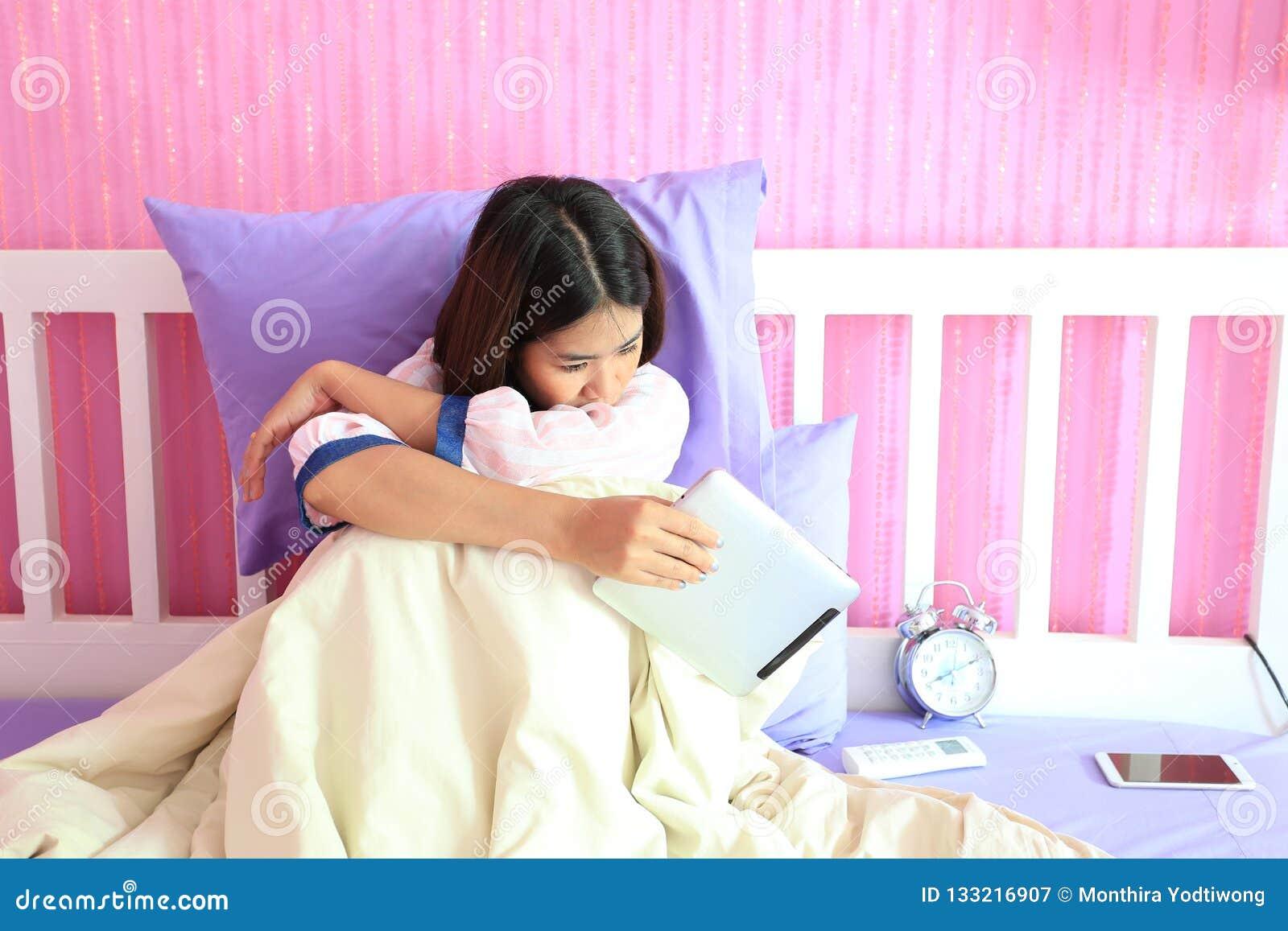 Giovane donna che esamina il dispositivo astuto della compressa con la sensibilità triste e
