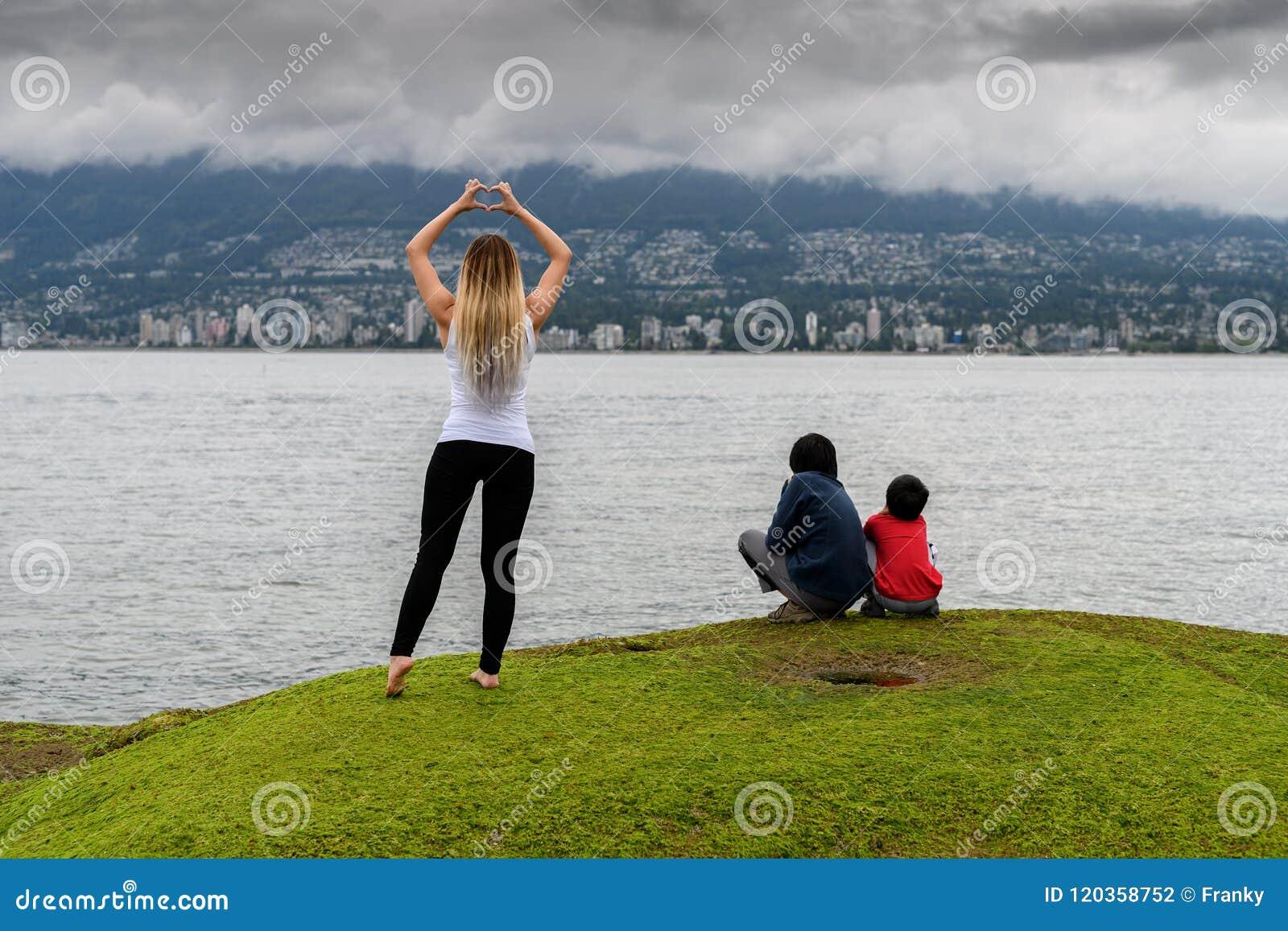 Giovane donna che fa forma del cuore con le mani in agai della città di Vancouver