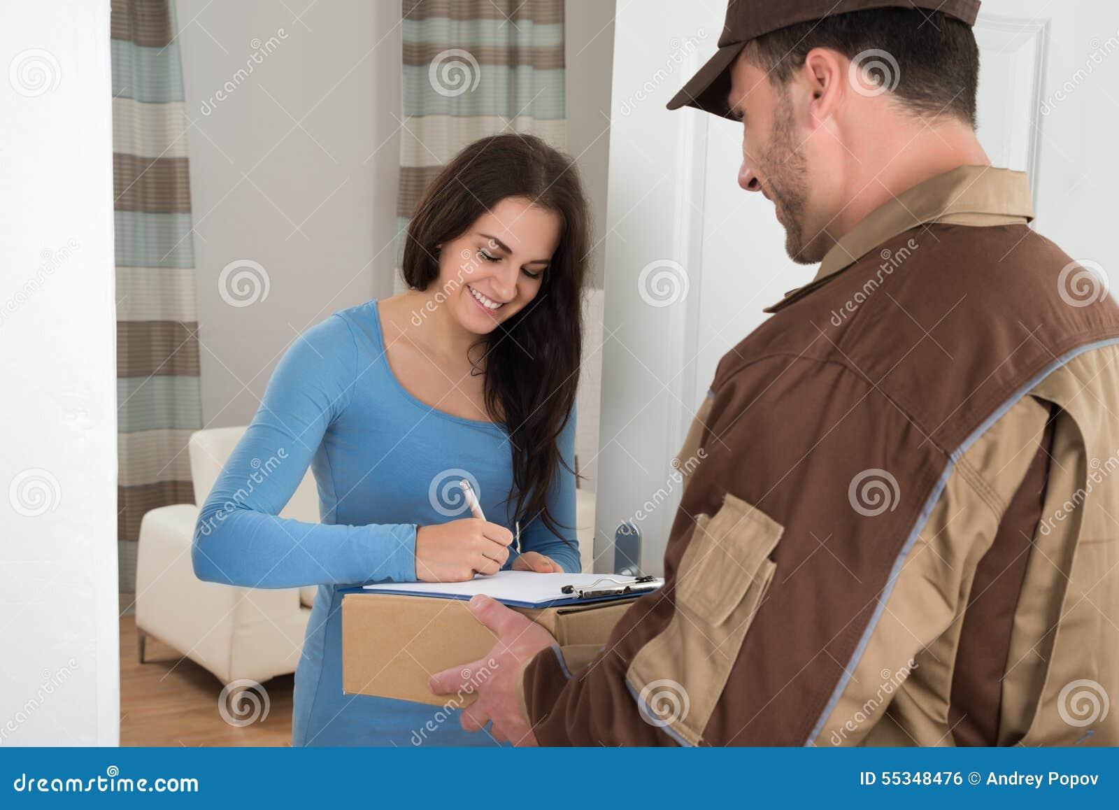 Giovane donna che firma mentre ricevendo corriere