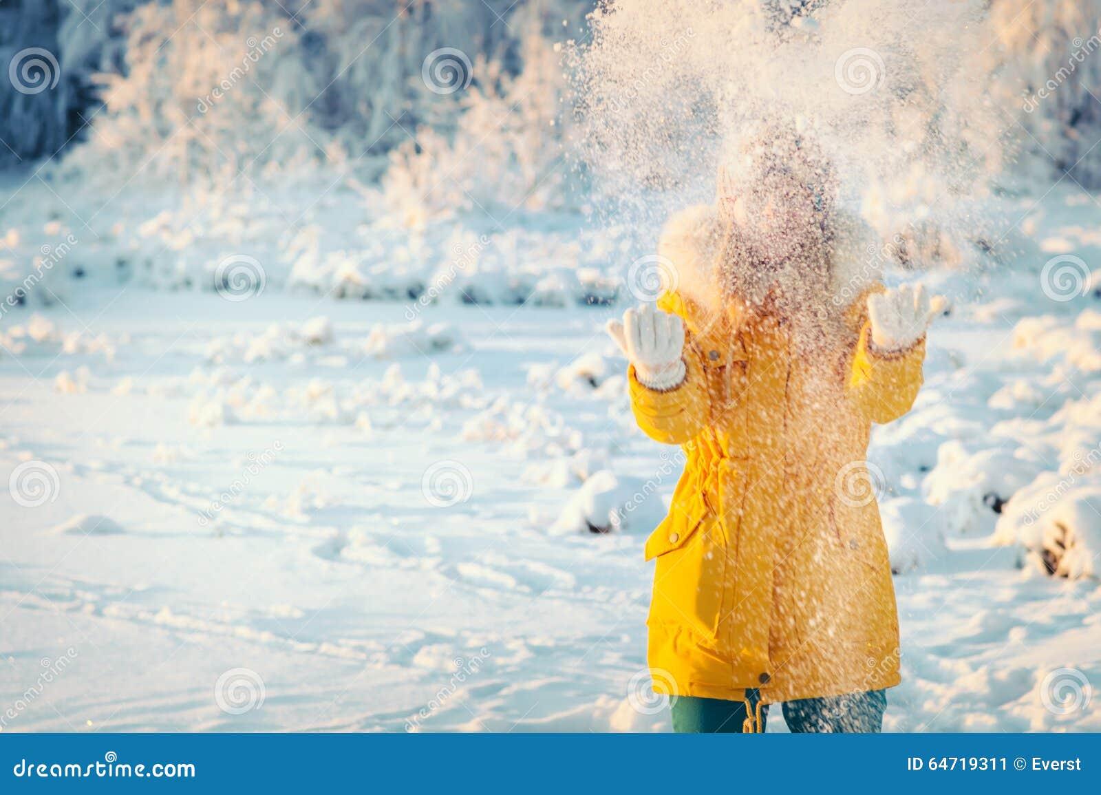 Giovane donna che gioca con lo stile di vita all aperto di inverno della neve
