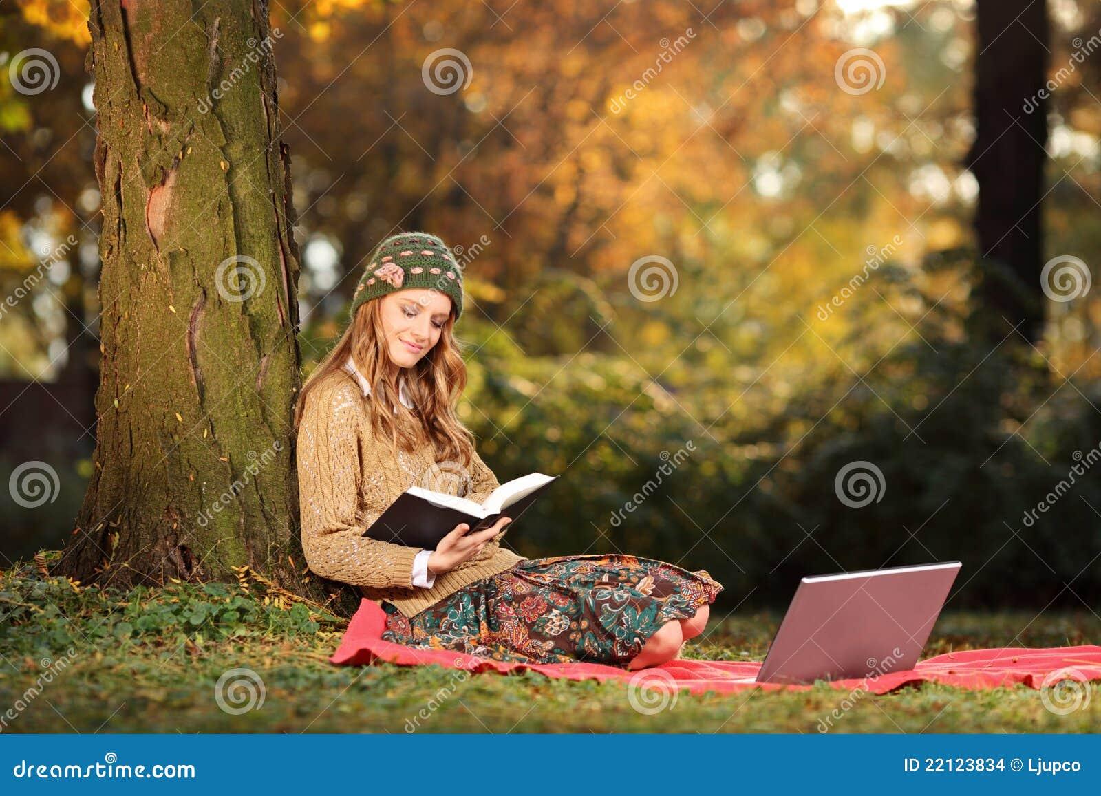 Giovane donna che legge un libro in una sosta fotografia for Foto di un libro