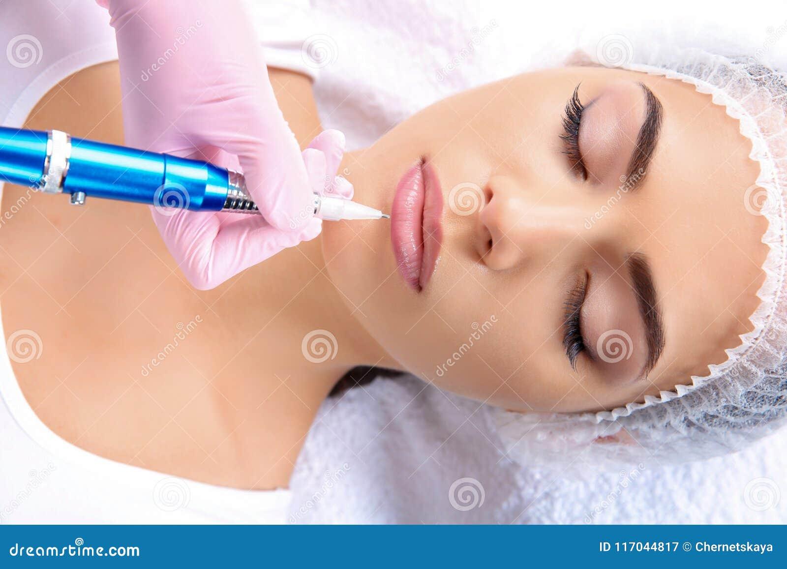 Giovane donna che ottiene trucco permanente sulle labbra