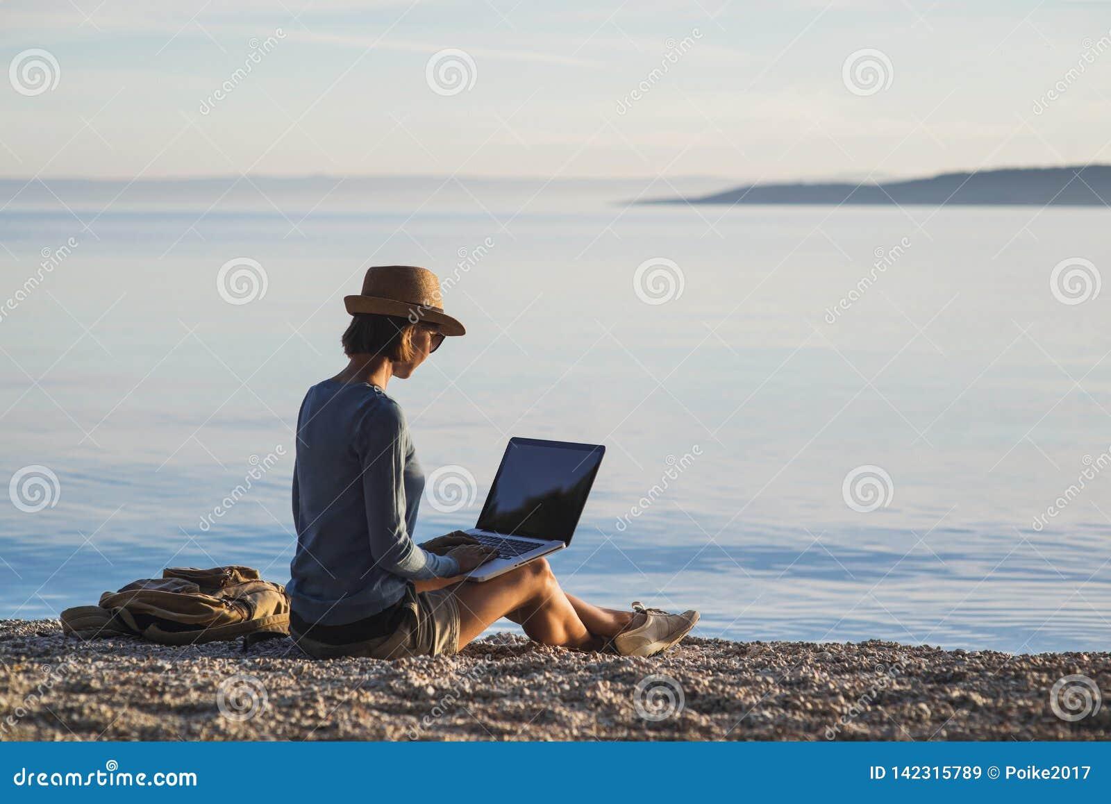 Giovane donna che per mezzo del computer portatile su una spiaggia Freelance il concetto del lavoro