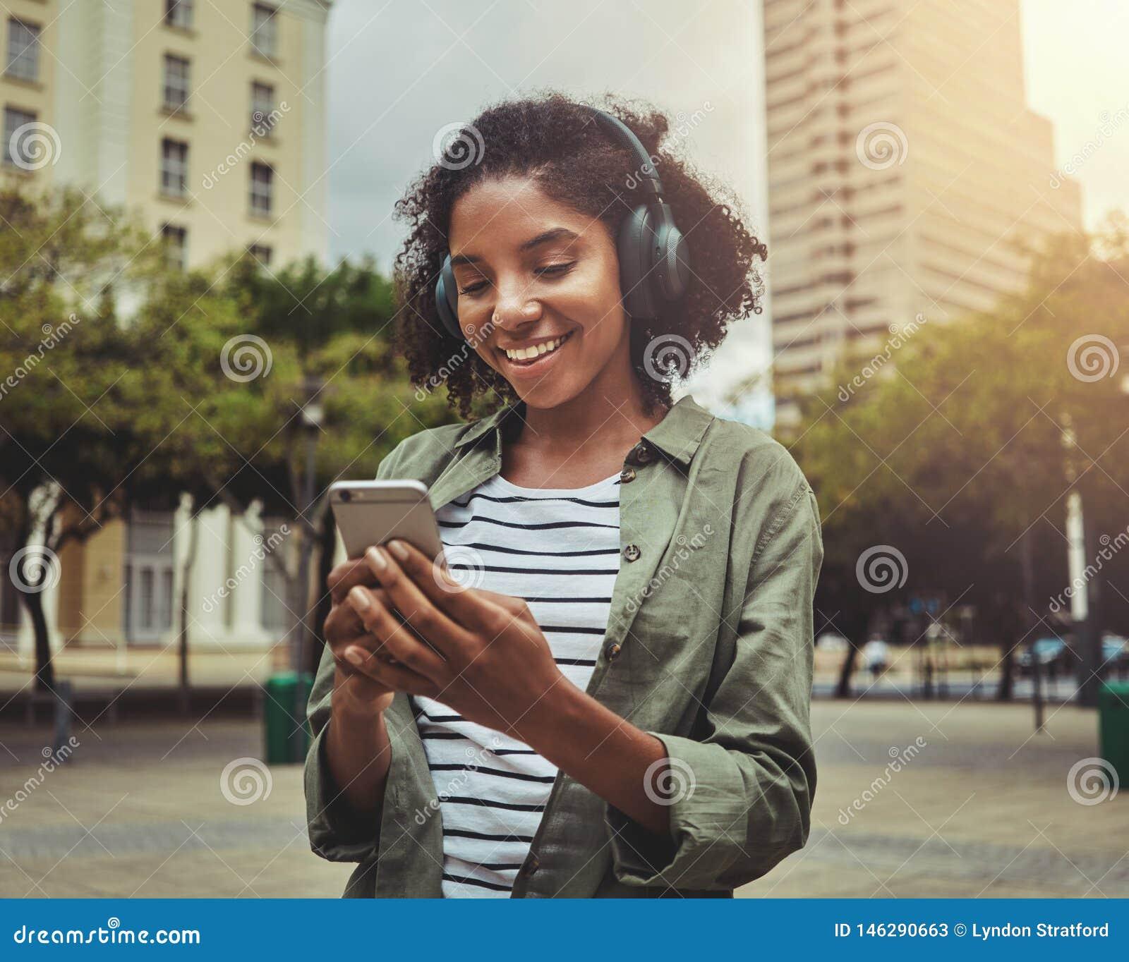 Giovane donna che per mezzo del telefono cellulare mentre ascoltando con le cuffie sulla sua testa
