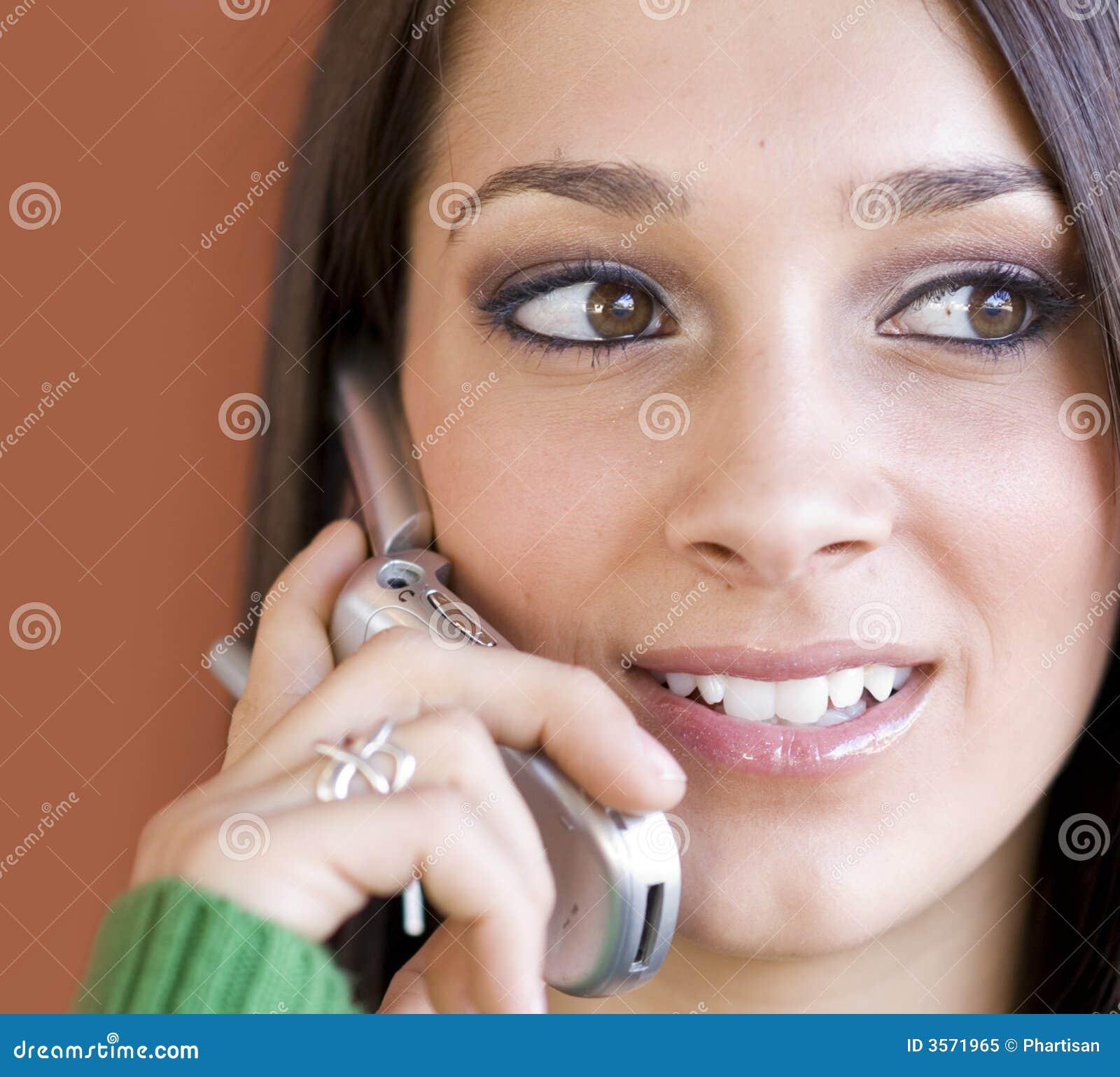 Giovane donna che per mezzo del telefono delle cellule