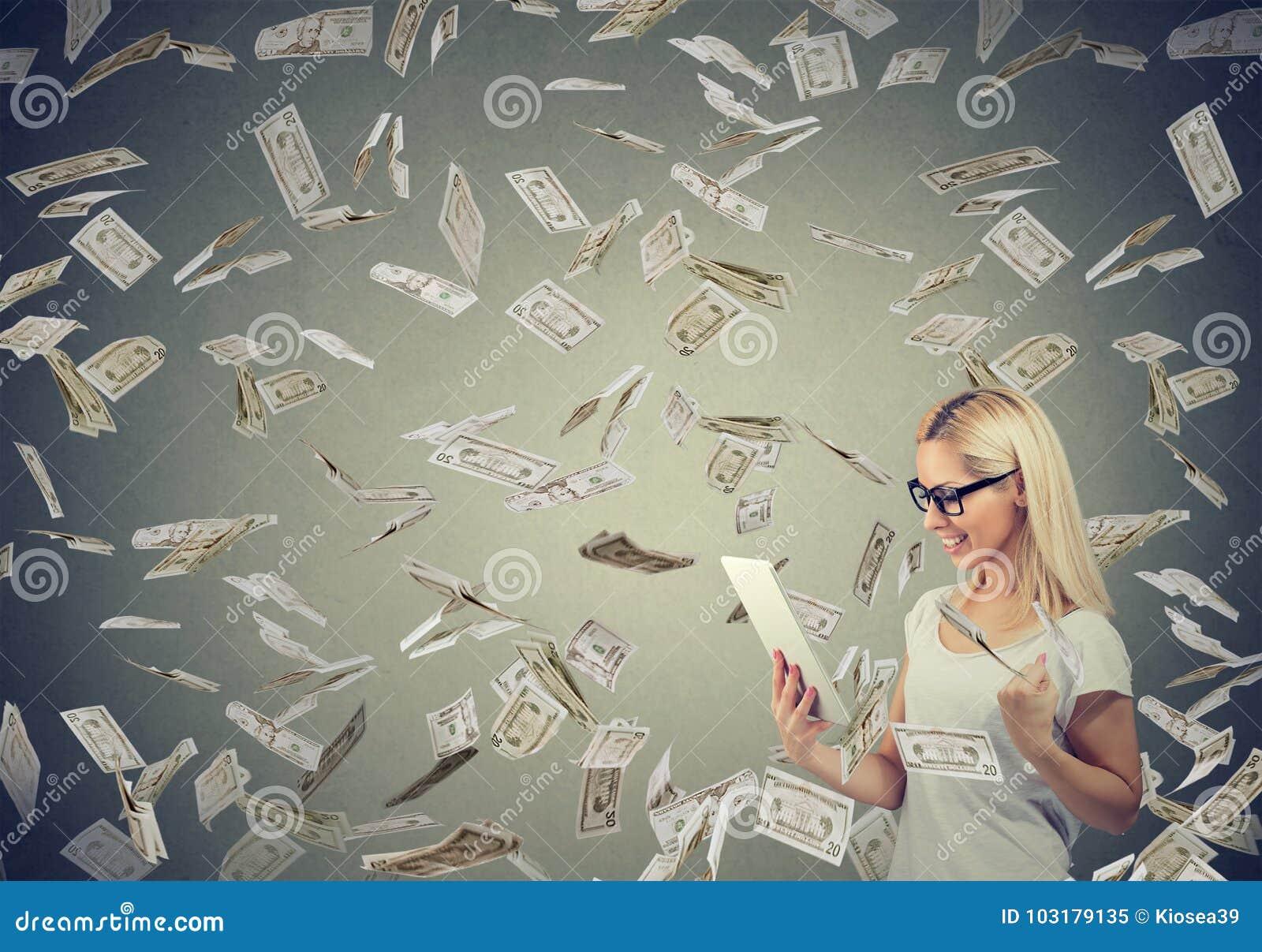 Giovane donna che per mezzo di una compressa che costruisce i soldi online dei guadagni di affari sotto i contanti che cadono