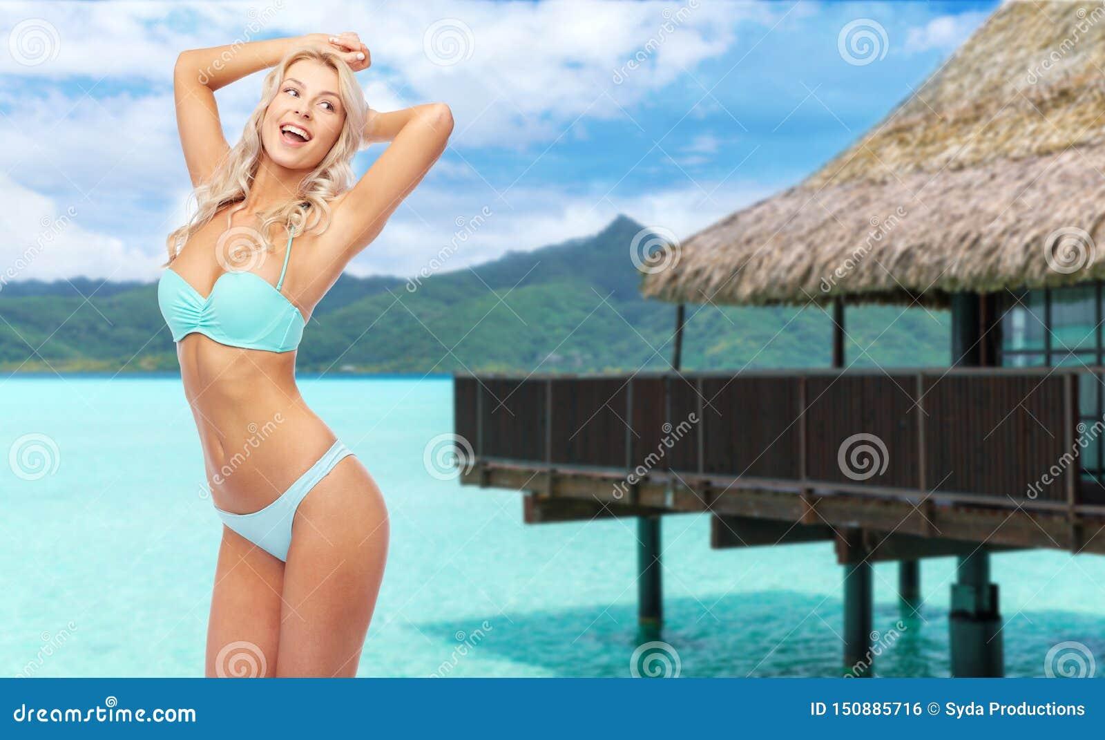 Giovane donna che posa in bikini sulla spiaggia