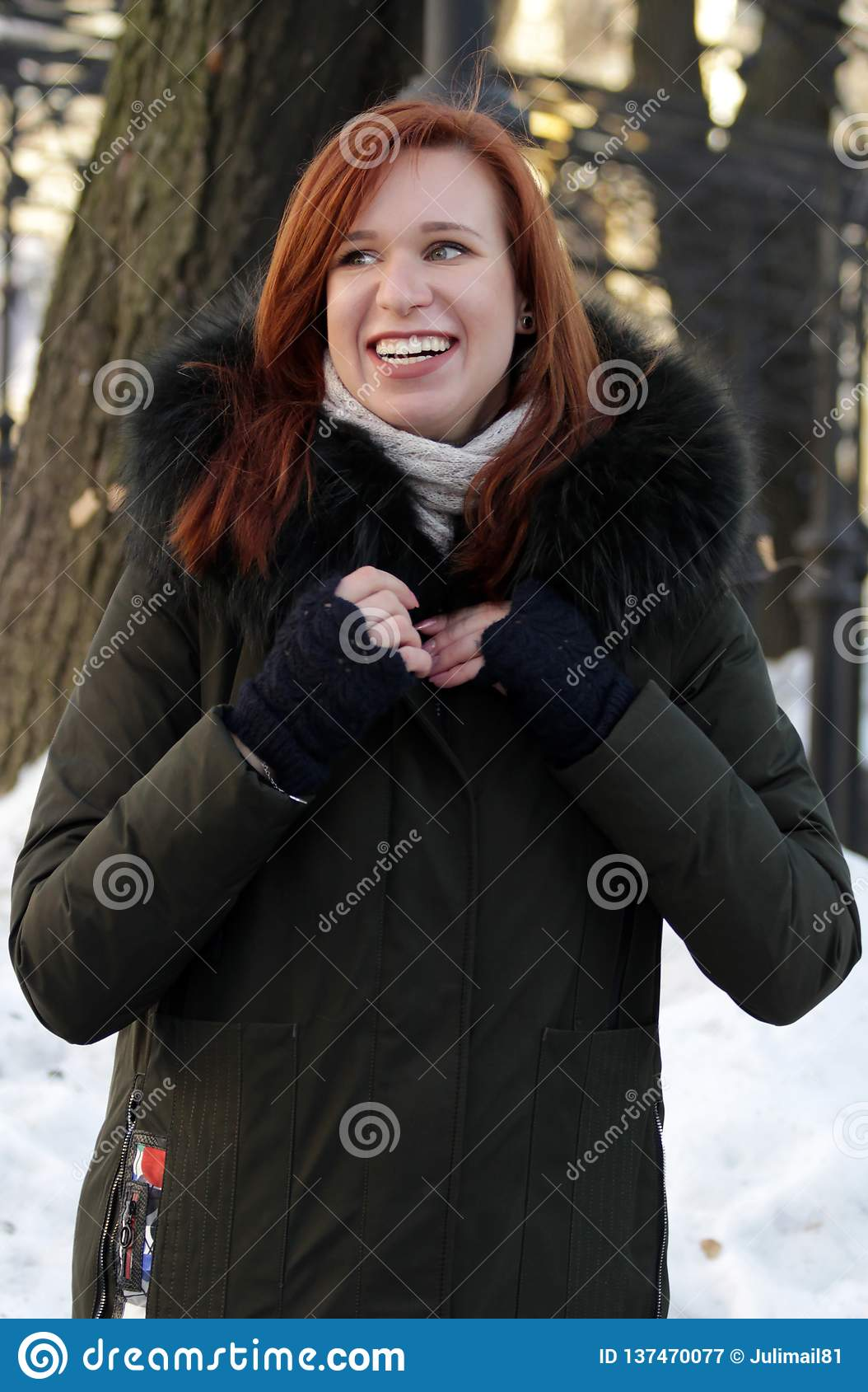 Giovane donna che posa sulla via nell inverno Stando in vestiti con un grande cappuccio della pelliccia Sorrisi della donna Sguar