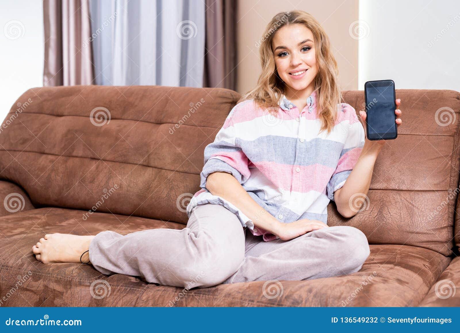 Giovane donna che presenta telefono cellulare