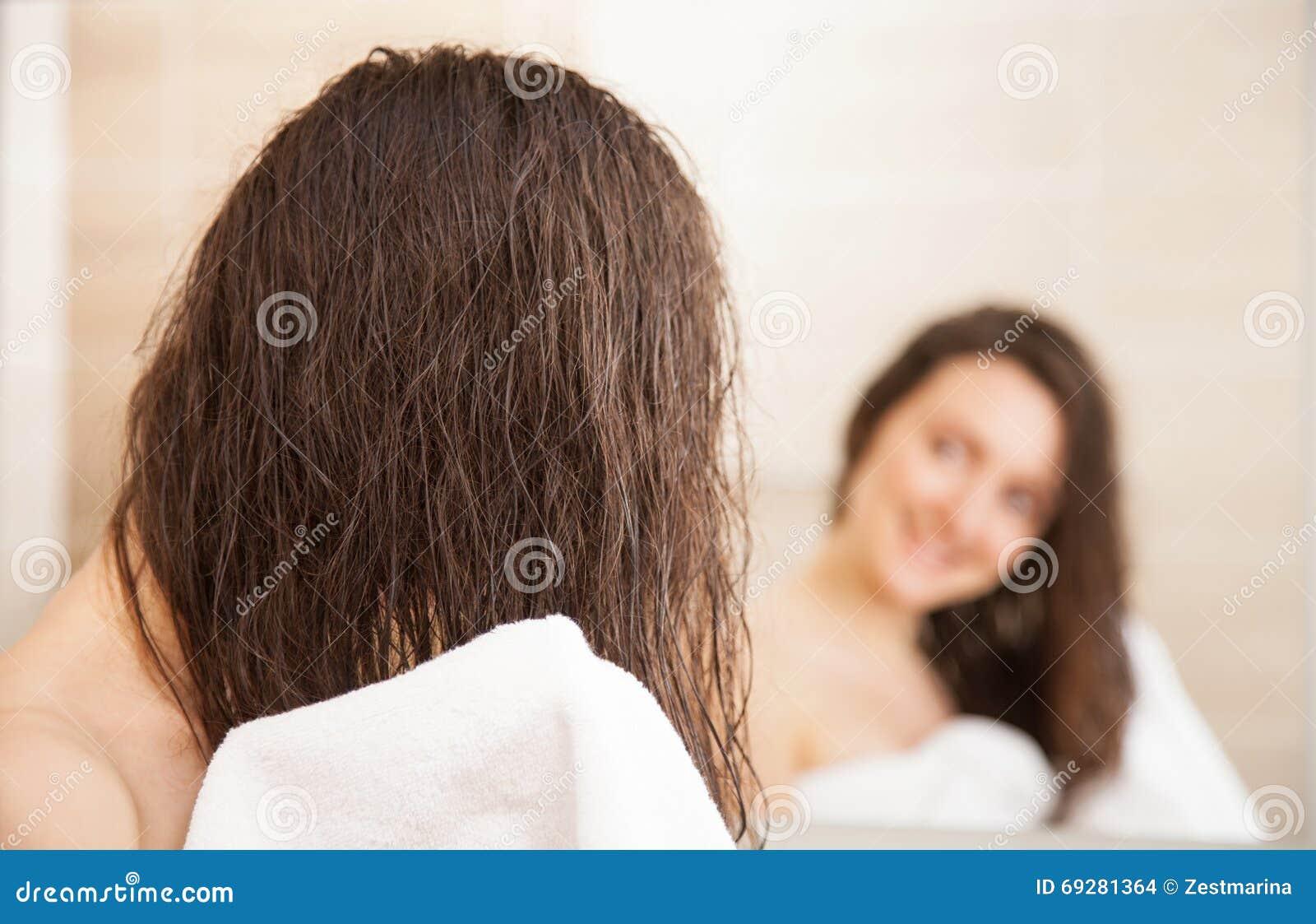 Giovane donna che pulisce capelli dopo una doccia