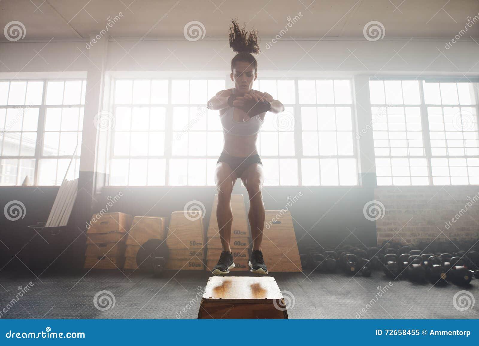 Giovane donna che risolve con una scatola alla palestra