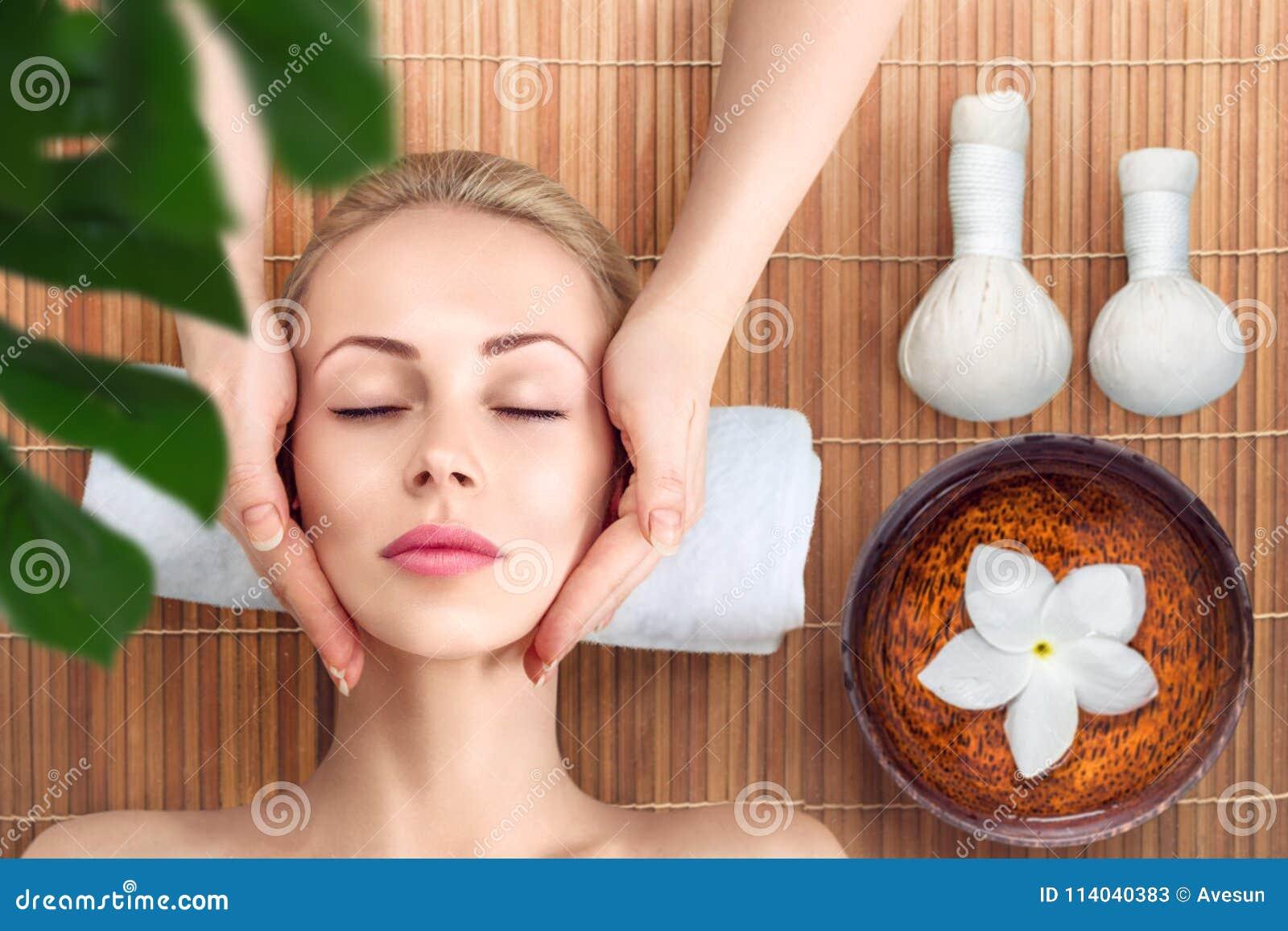 Giovane donna che si rilassa con il massaggio in stazione termale