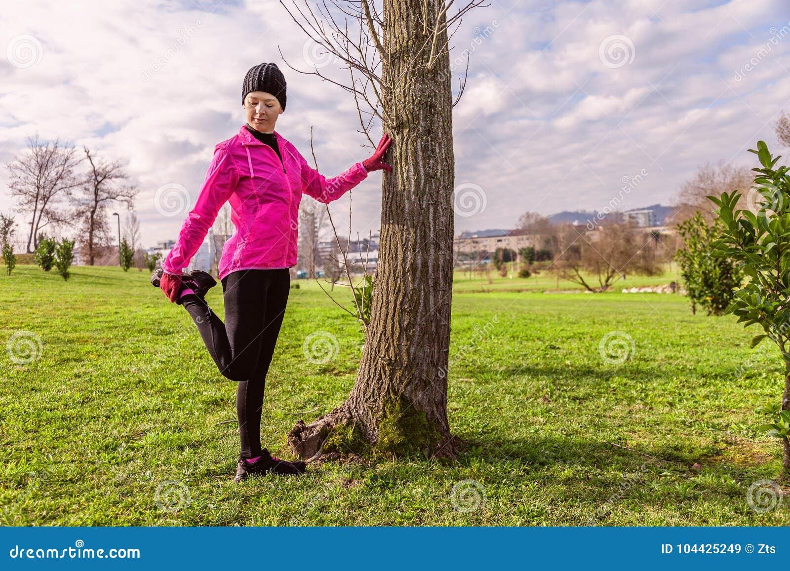 Giovane donna che si scalda e che allunga le gambe prima dell correre su un inverno freddo, autunno del giorno dell autunno in un